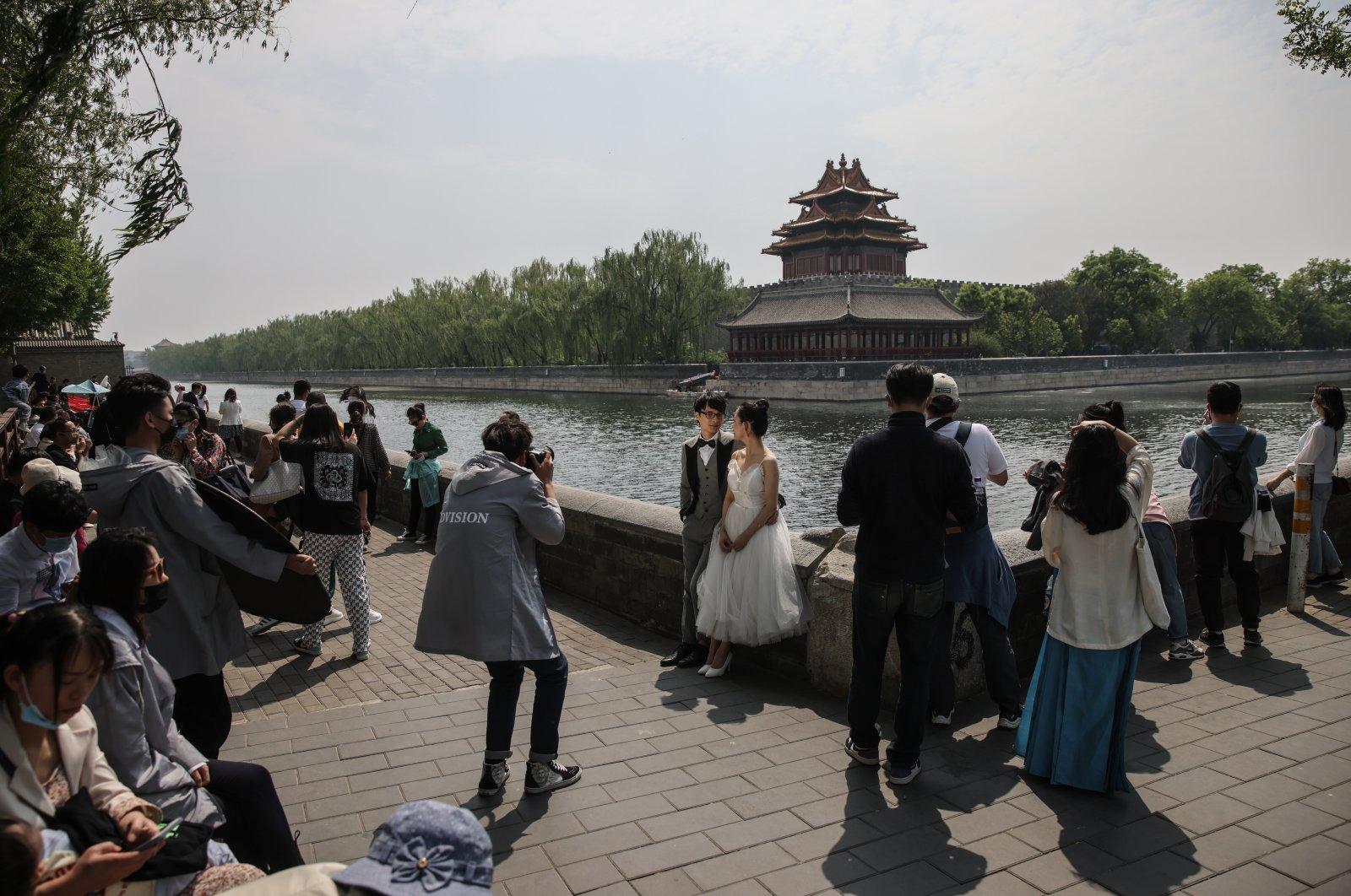 A couple pose for their pre-wedding photos near the Forbidden City in Beijing, China, May 3, 2021. (EPA Photo)