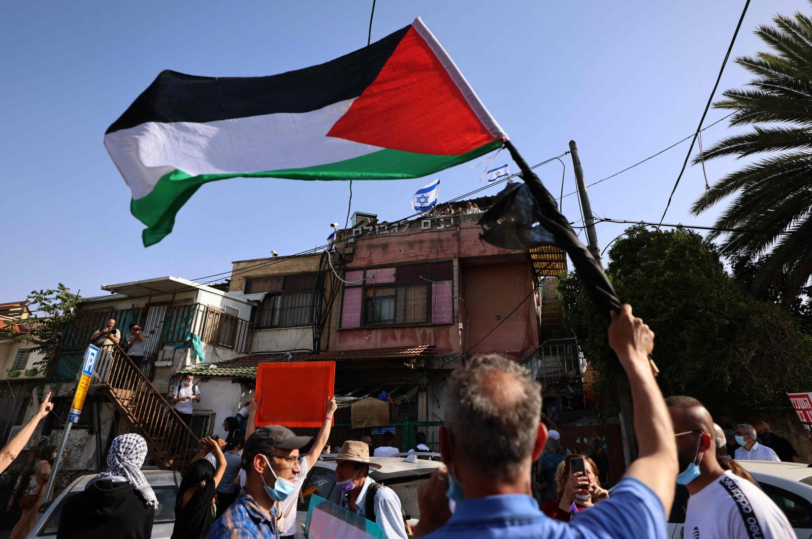 Palestinian and Israeli activists gather in front of Israeli settlers' houses during a demonstration against the expulsion of Palestinian families from their homes, in the Palestinian neighbourhood of Sheikh Jarrah in Israeli-annexed East Jerusalem, April 16, 2021. (AFP Photo)
