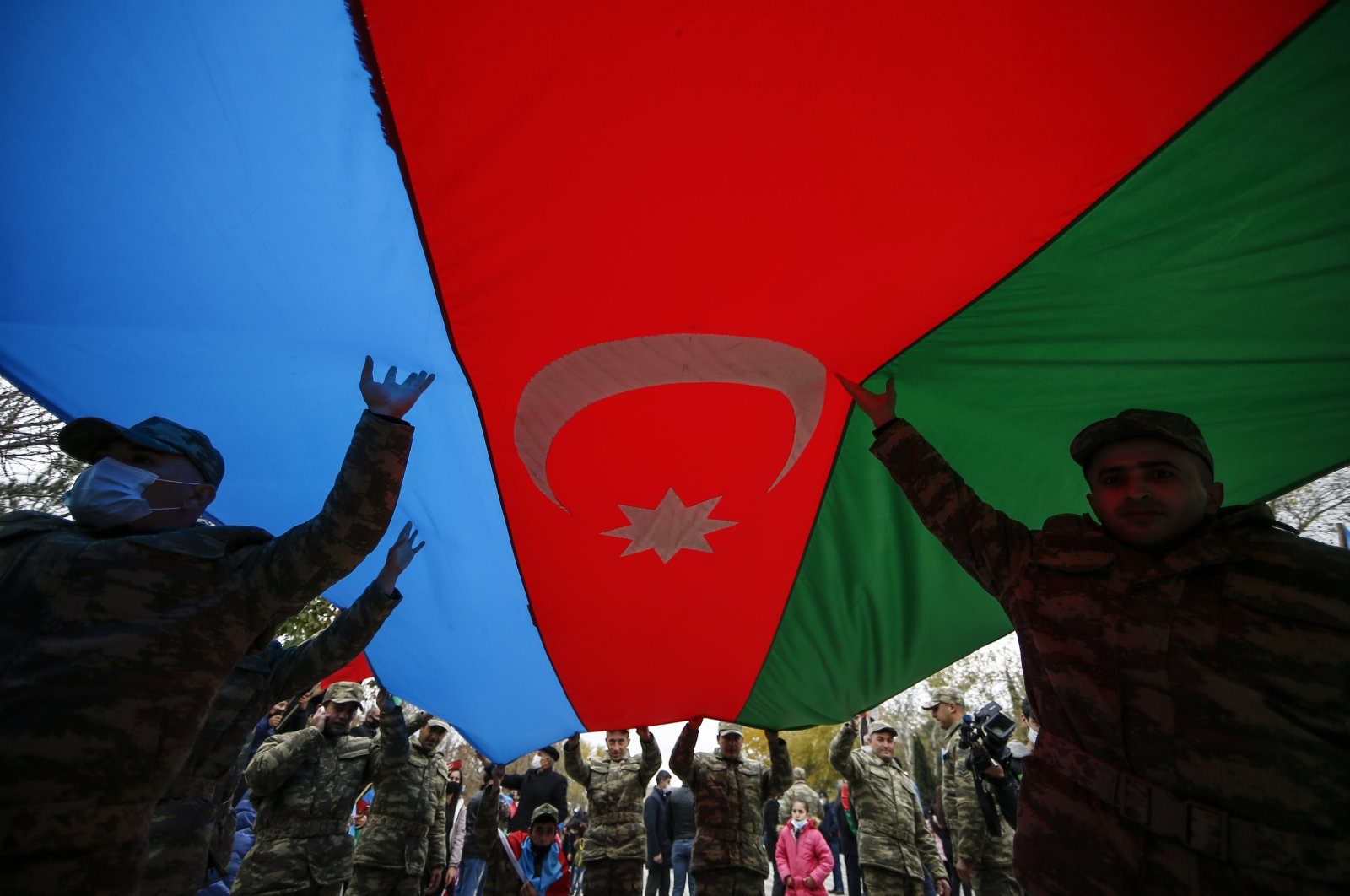 Azerbaijani soldiers carry a huge national flag as they celebrate the transfer of the Lachin region to Azerbaijan's control, as part of a peace deal that required Armenian forces to cede the Azerbaijani territories they held outside Nagorno-Karabakh, in Aghjabadi, Azerbaijan, Dec. 1, 2020. (AP Photo)