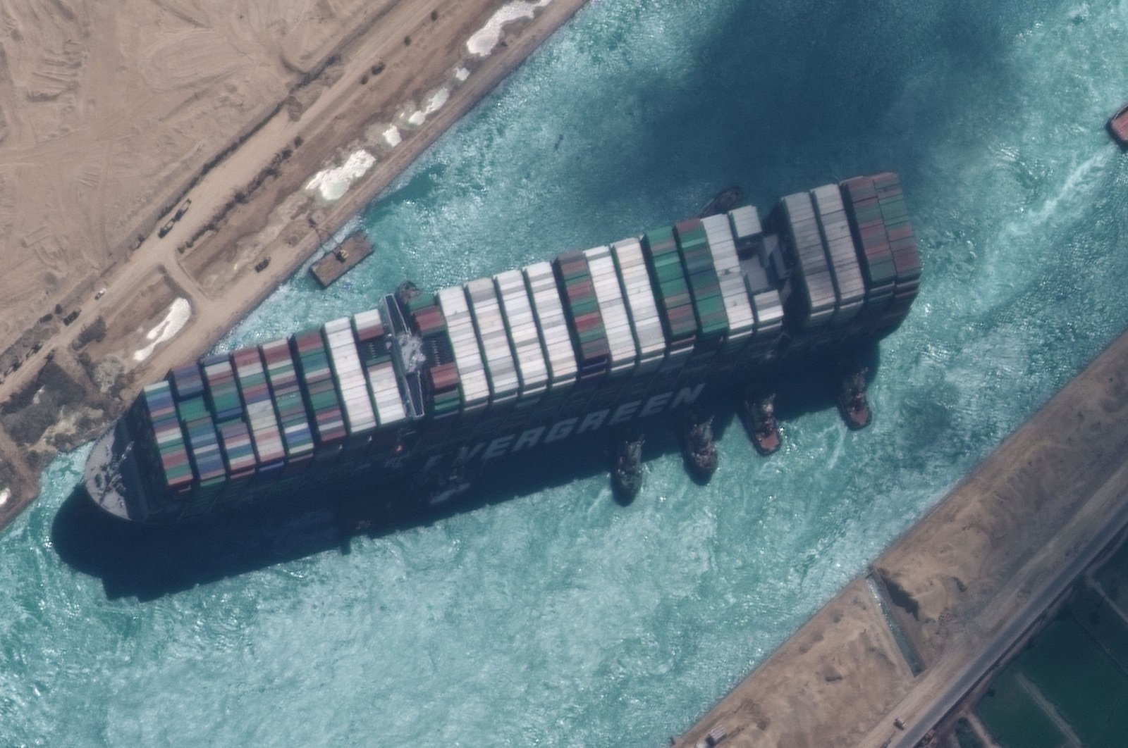 Tugboats try to reposition the Ever Given container ship in the Suez Canal, Egypt, March 29, 2021. (MAXAR Technologies via EPA)