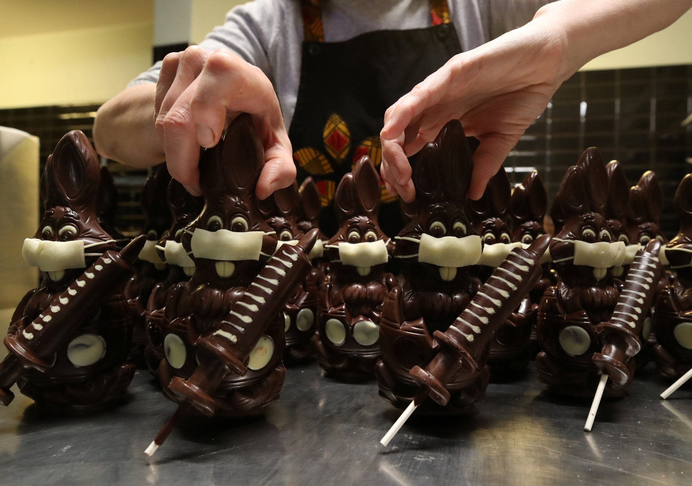 Belgian artisan chocolate maker Genevieve Trepant worksonchocolate bunnieswearing a protective mask and holding a vaccine syringe called 'L'Atch'a Azteka' at her workshop, Cocoatree in Lonzee, Belgium, April 30, 2021. (Reuters Photo)