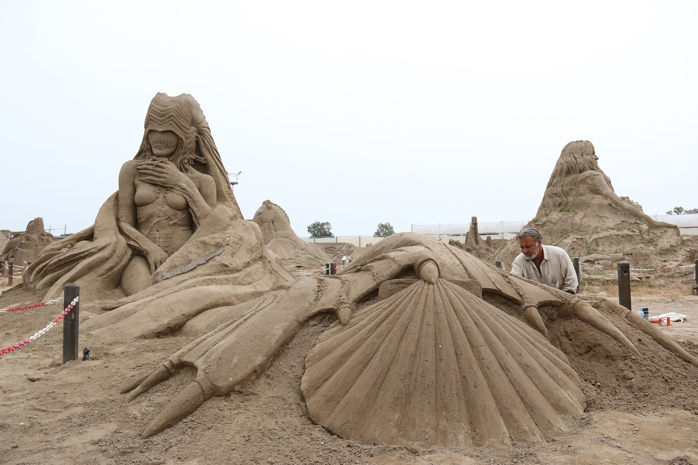 A sculptor works on his sand sculpture for the International Sand Sculpture Festival, Antalya, southern Turkey, May 4, 2021. (IHA Photo)