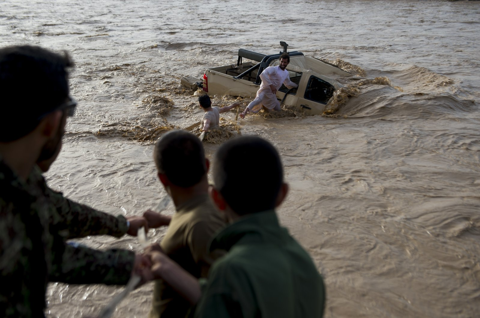 In this file photo from April 23, 2013, two men with help from a crowd attempt attach a tow line to an Afghan Army truck that was swept away by floodwaters. (Getty Images)