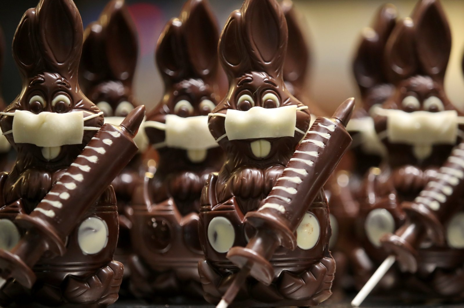"""Chocolate bunnies wearing protective masks and holding vaccine syringes called """"L'Atch'a Azteka"""" are seen at artisan Genevieve Trepant's workshop, Cocoatree in Lonzee, Belgium, April 30, 2021. (Reuters Photo)"""