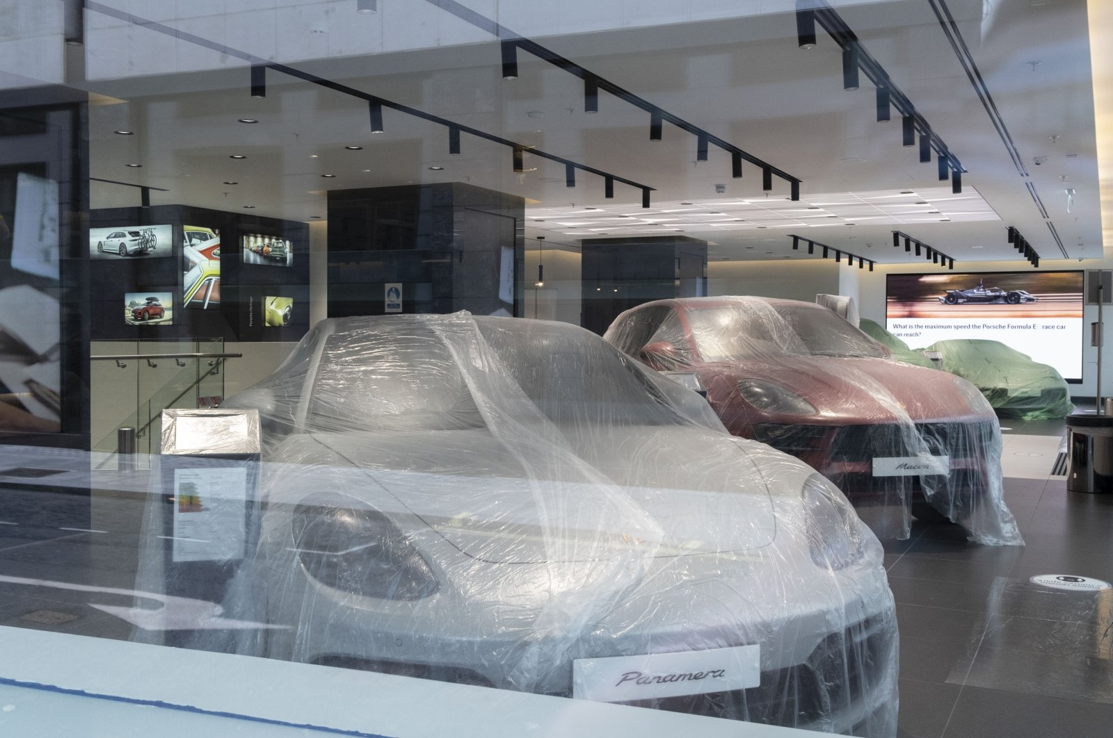 Protected from dust as non-essential businesses closed during the coronavirus pandemic, luxury Porsche cars are covered up in the company's Piccadilly showroom, London, England, March 4, 2021. (Getty Images)