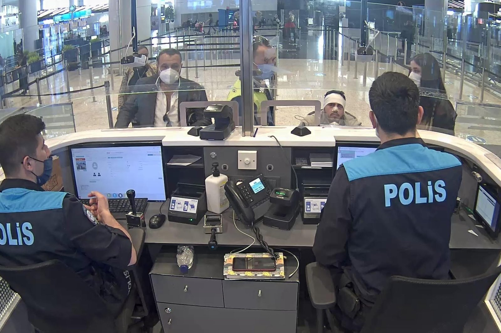 Security camera footage shows police officers questioning an illegal migrant with a bandaged head, in Istanbul, Turkey, May 5, 2021. (İHA PHOTO)