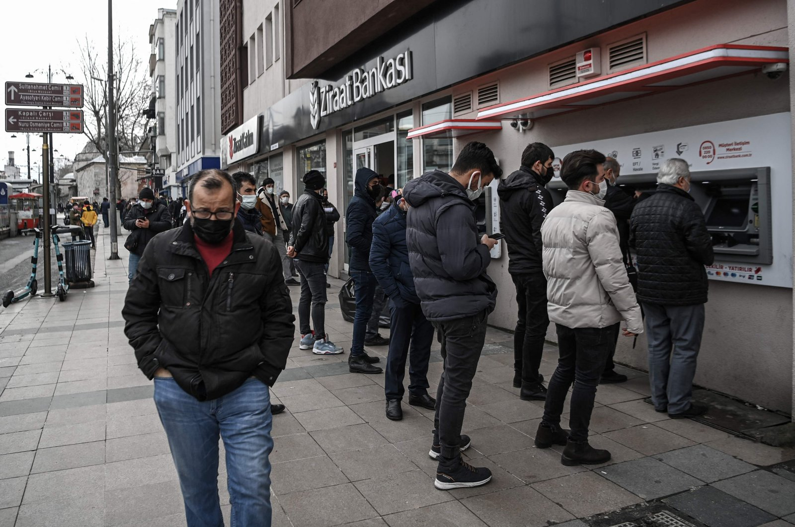 Customers wait in line to use the ATMs of a Turkish bank near the Grand Bazaar in Istanbul, Turkey, March 22, 2021. (AFP Photo)