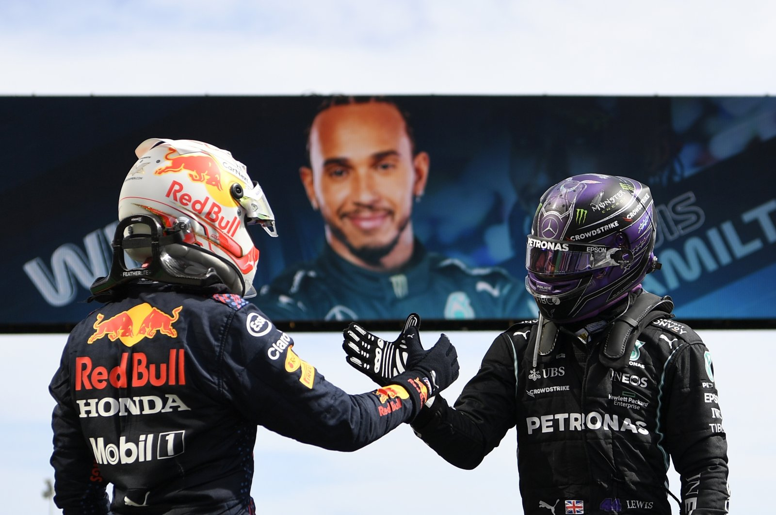 Mercedes driver Lewis Hamilton of Britain (R) shakes hands with Red Bull's Max Verstappen after winning the Portugal Formula One Grand Prix at the Algarve International Circuit near Portimao, Portugal, May 2, 2021. (AP Photo)