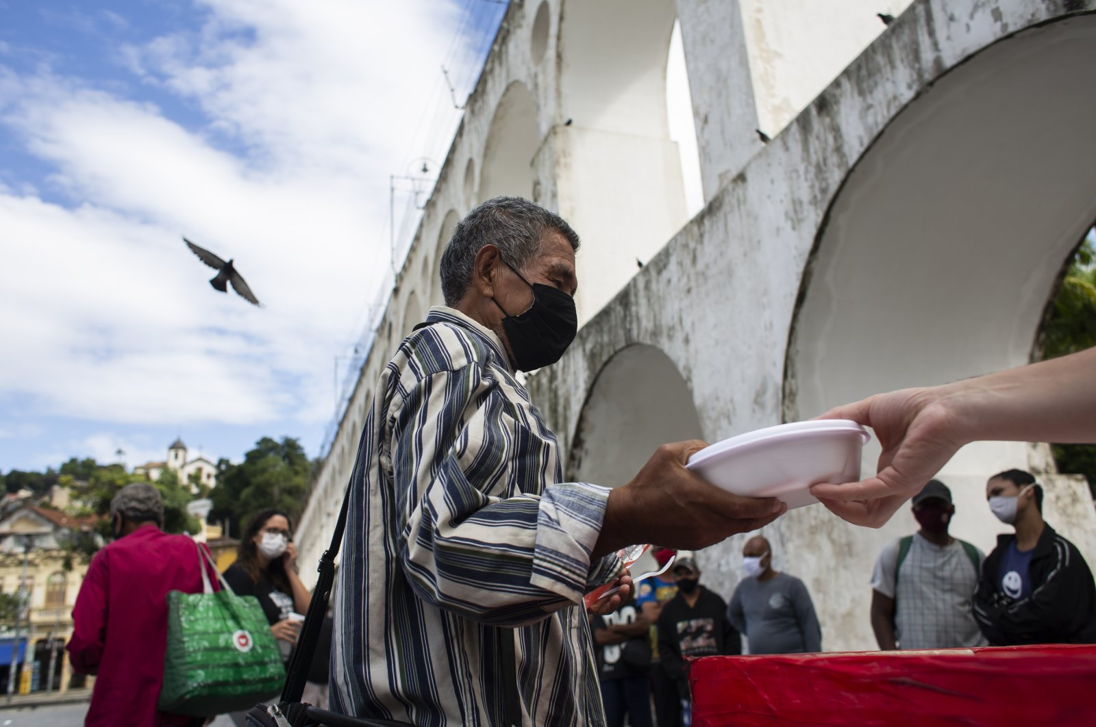People line up for free meals delivered by Covid Without Hunger group of volunteers, in Rio de Janeiro, Brazil, Apr. 29, 2021. (AP PHOTO)