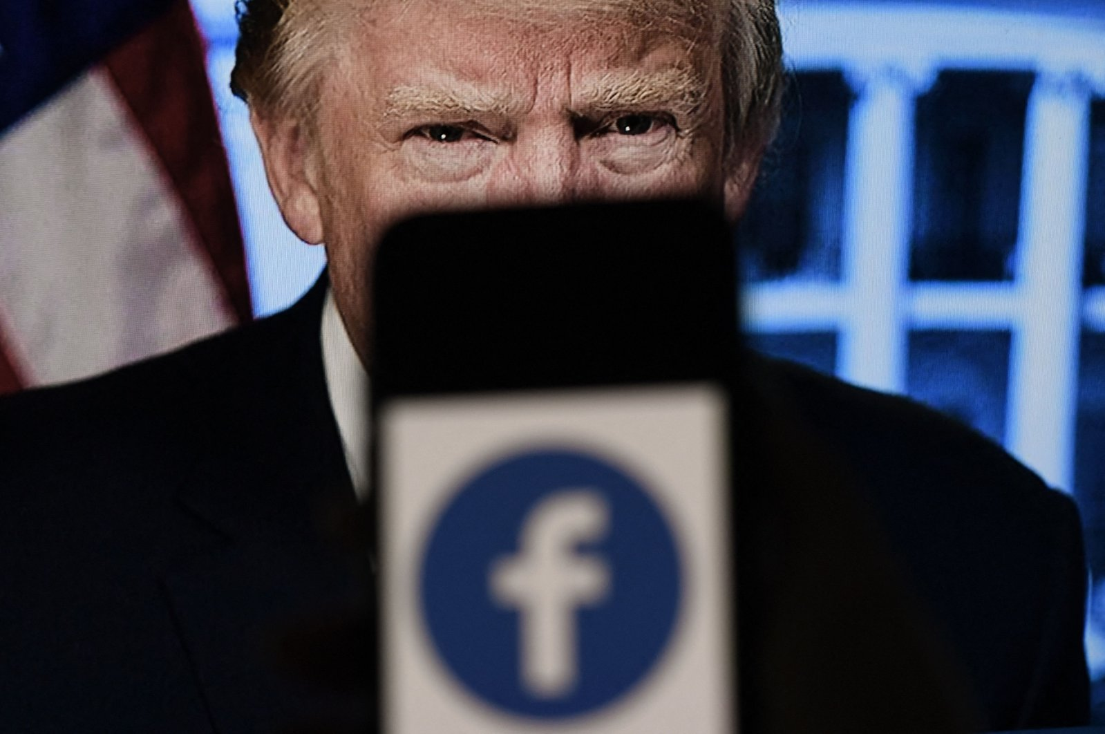 In this file photo illustration, a phone screen displays a Facebook logo with the official portrait of former US President Donald Trump in the background, Arlington, Virginia, on May 4, 2021. (AFP Photo)