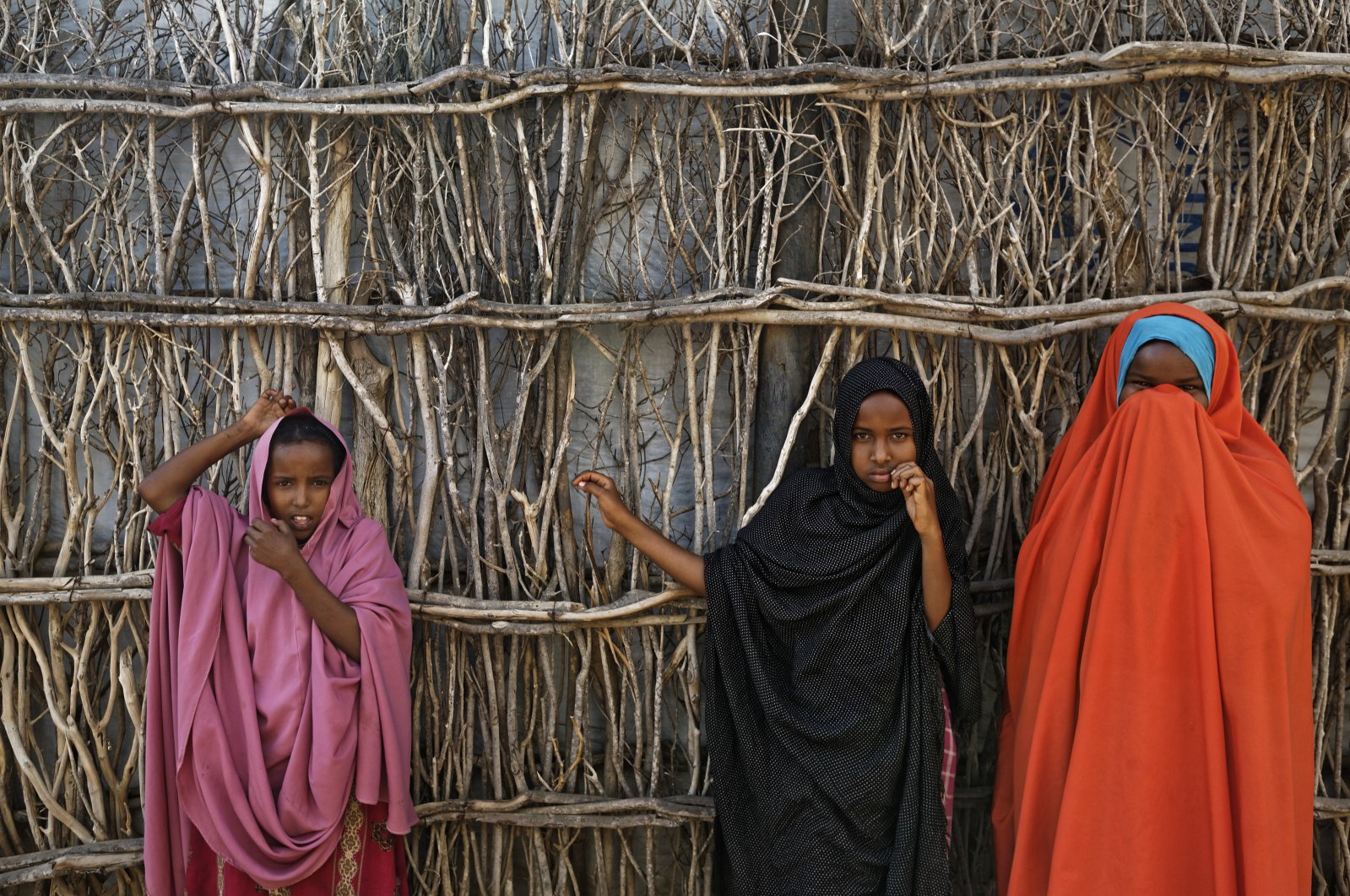 Somali refugee girls stand by the fence surrounding their hut at the Dadaab refugee camp, northern Kenya, Dec. 19, 2017. (AP Photo)