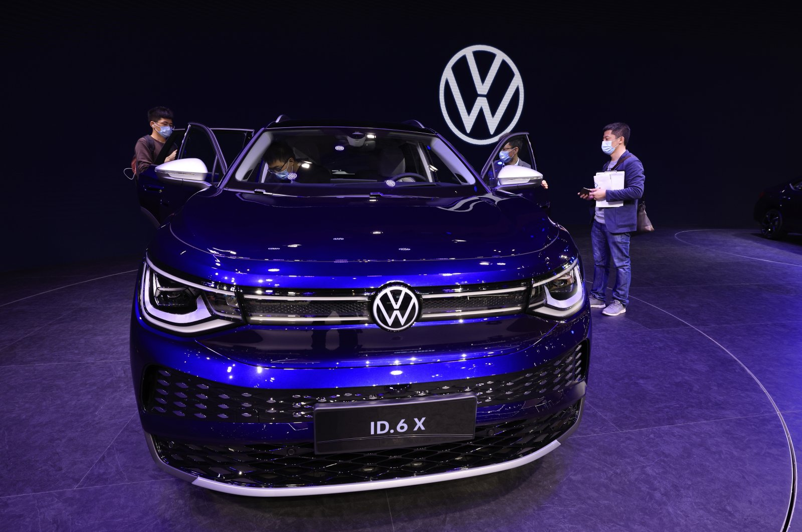 Visitors look at the latest electric car from Volkswagen during the Shanghai Auto Show in Shanghai, China, April 20, 2021. (AP Photo)