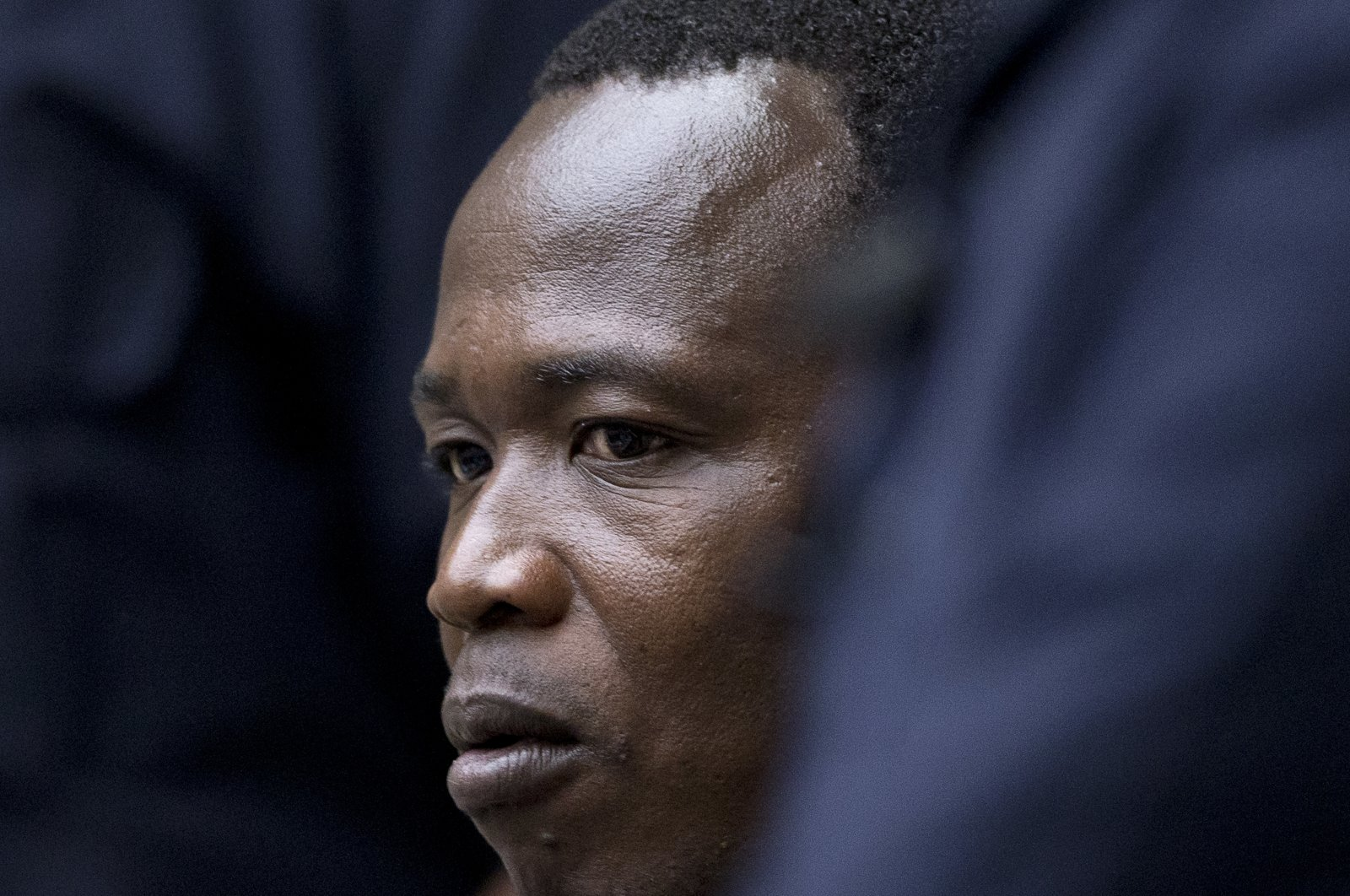 Dominic Ongwen, a senior commander in the Lord's Resistance Army, whose fugitive leader Kony is one of the world's most-wanted war crimes suspects, is flanked by two security guards as he sits in the courtroom of the International Court in The Hague, Netherlands, Dec. 6, 2016. (AP Photo)