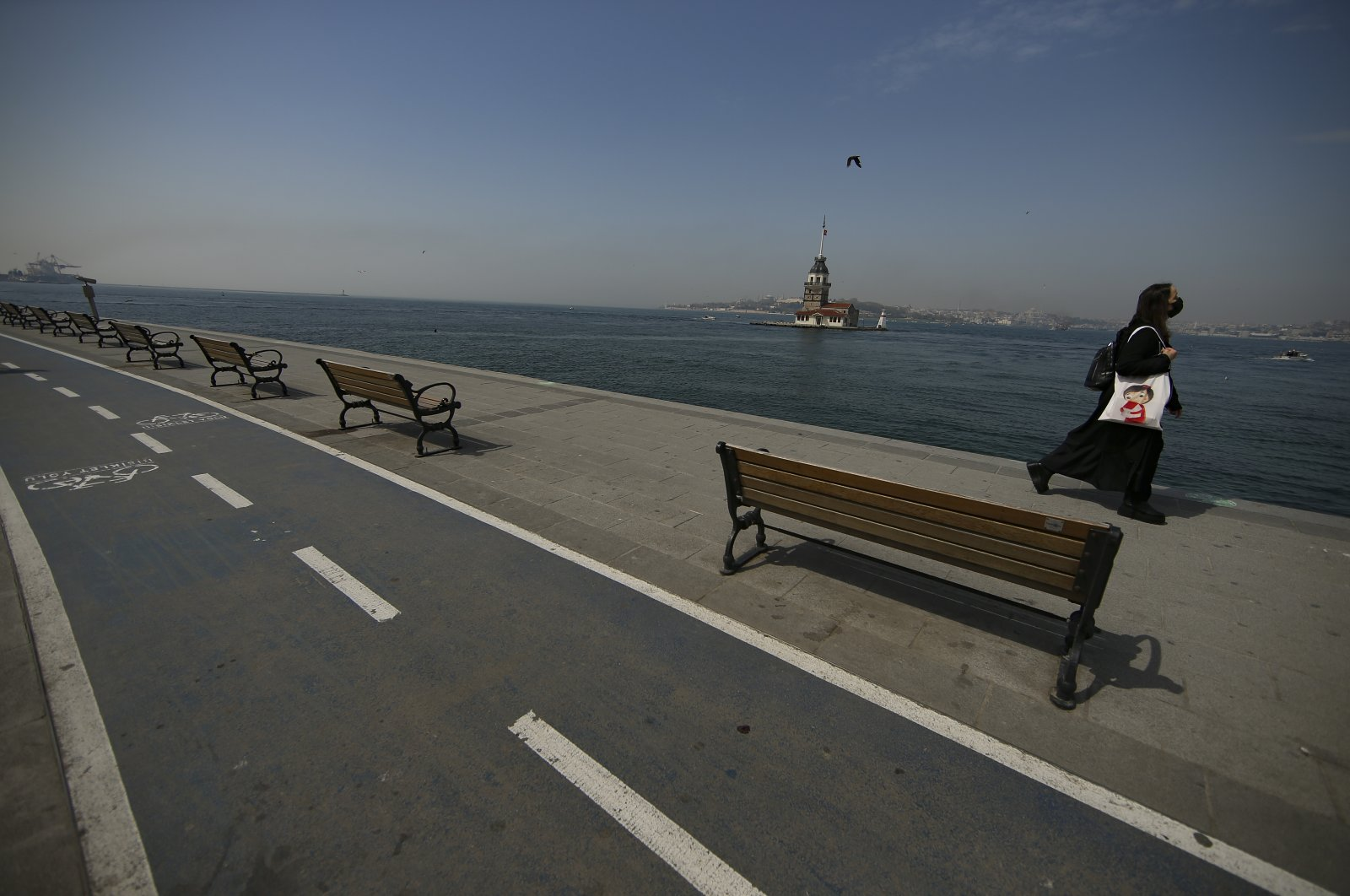 Backdropped by the Maiden's Tower a woman walks on a nearly deserted promenade by the Bosphorus Strait in Istanbul, Friday, April 30, 2021, on the first day of a tight lockdown to help protect from the spread of the coronavirus. (AP Photo)