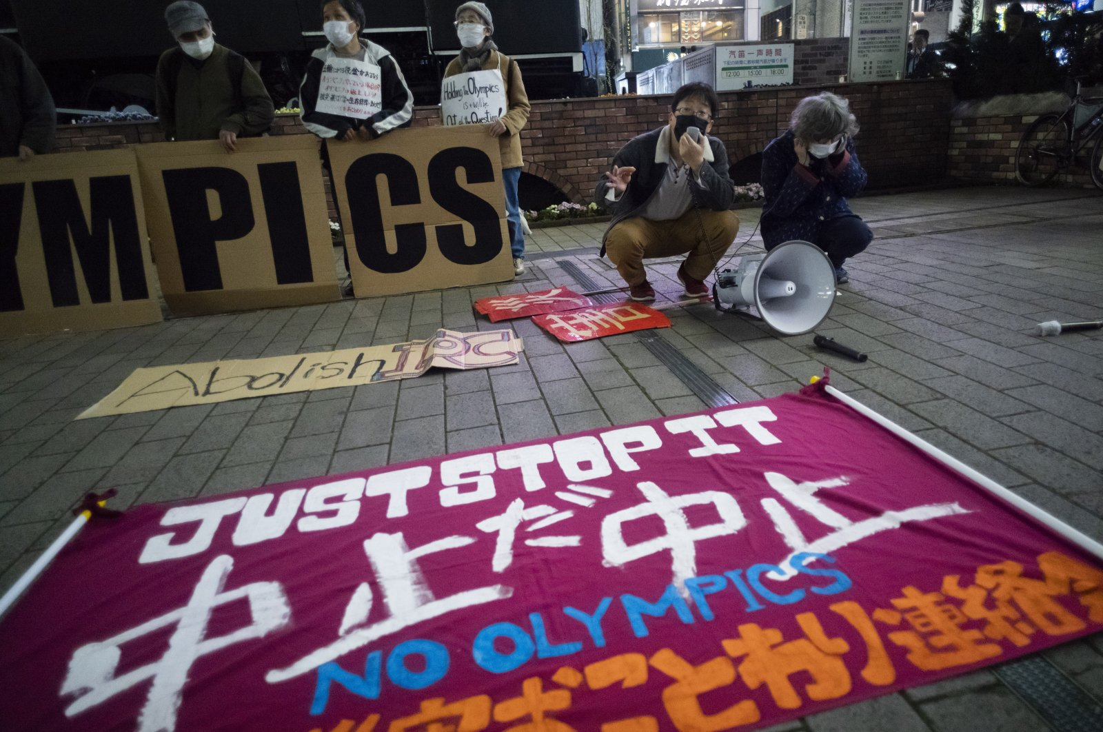 """Protesters place a """"No Olympics"""" banner in Tokyo during a demonstration against the Tokyo 2020 Olympic and Paralympic Games, March 25, 2021."""