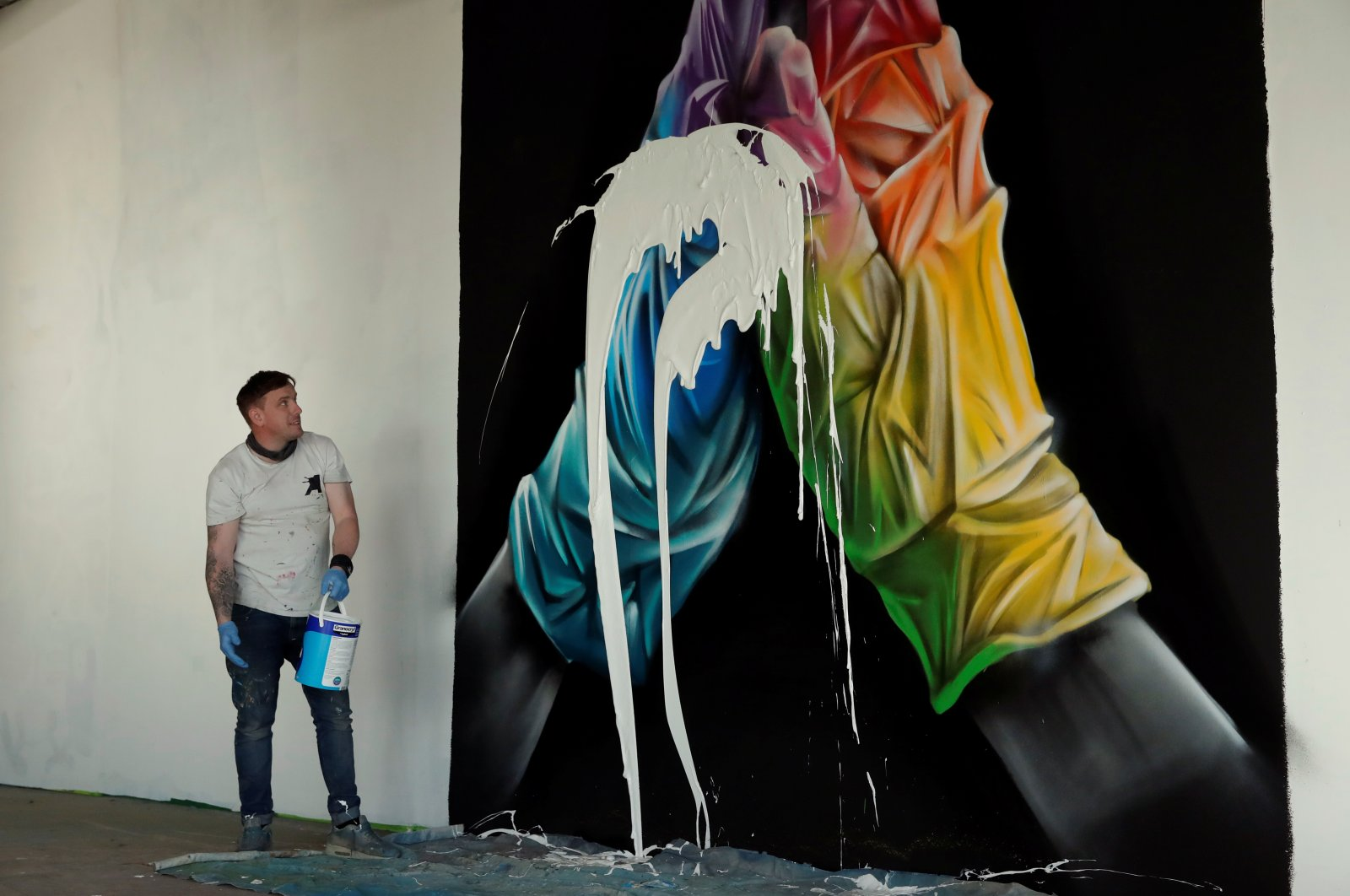 Street artist Nathan Murdoch looks at the artwork with paint splattered over it, as he creates a piece of crypto art to be auctioned with proceeds donated to the NHS in Peterborough, Britain, April 15, 2021. (Reuters Photo)