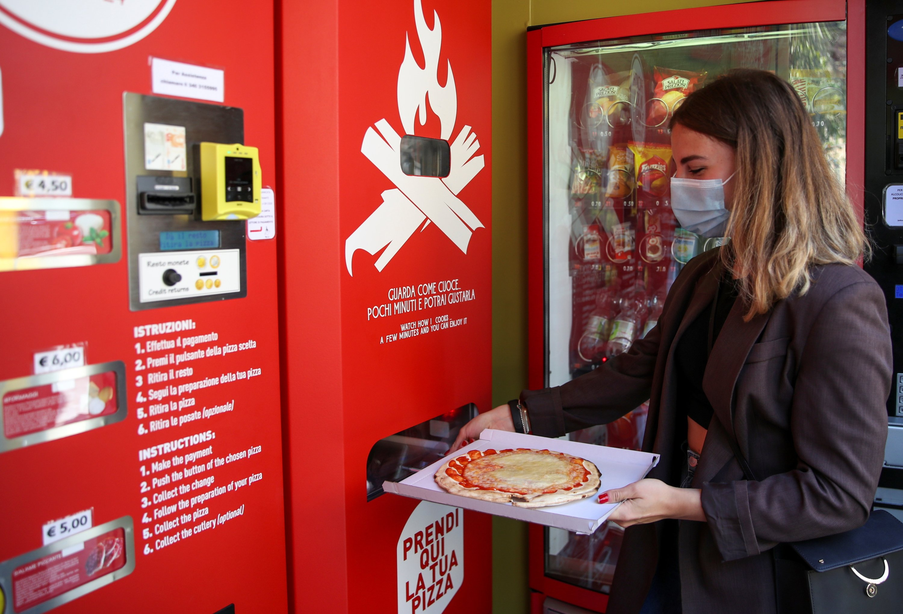 Fabrizia Pugliese collects her order at the first automatic pizza vending machine, which is capable of kneading, seasoning and cooking the pizza in three minutes, in Rome, Italy, May 6, 2021. (Reuters Photo)