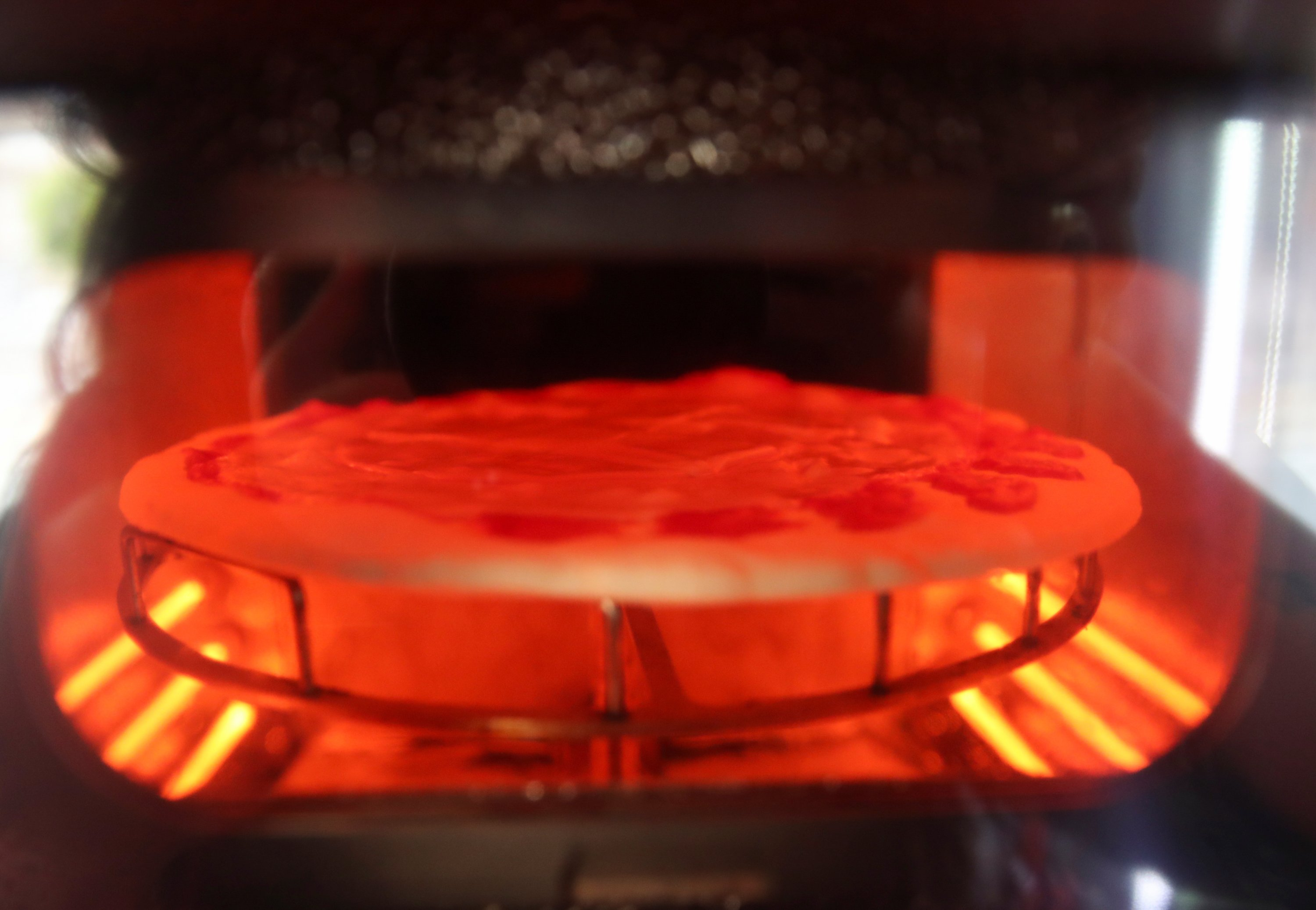 A pizza being baked is seen in the first automatic pizza vending machine, which is capable of kneading, seasoning and cooking the pizza in three minutes, in Rome, Italy, May 6, 2021. (Reuters Photo)