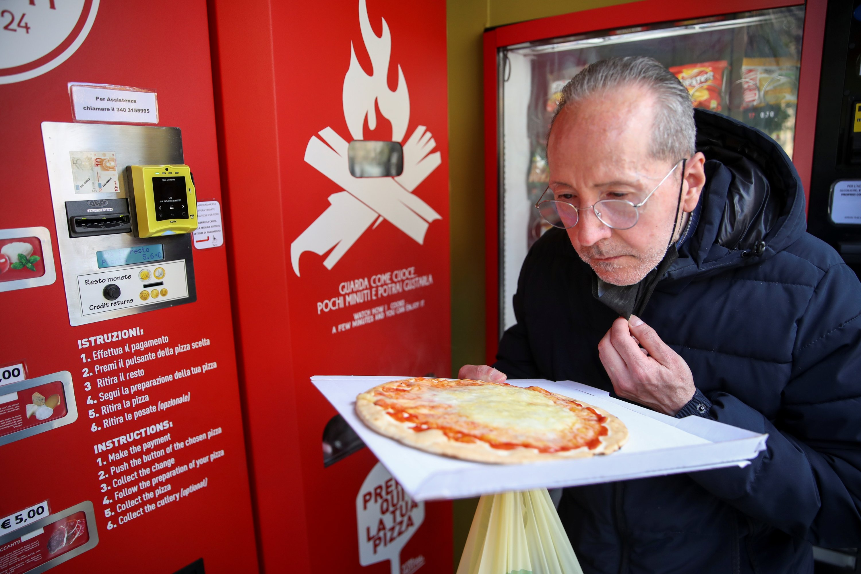 Claudio Zampiga sniffs his pizza at the first automatic pizza vending machine, which is capable of kneading, seasoning and cooking the pizza in three minutes, in Rome, Italy, May 6, 2021. (Reuters Photo)