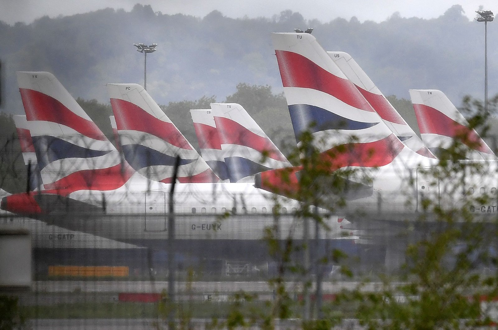 Aircraft grounded due to the COVID-19 pandemic, including planes operated by British Airways, stand on the apron at London Gatwick Airport near Crawley, southern England, May 1, 2020. (AFP Photo)