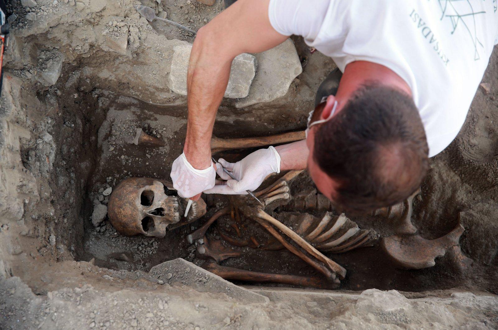 An archeologist works on a skeleton found at the Kadıkalesi archaeological site, Aydın, western Turkey, May 6, 2021. (AA Photo)