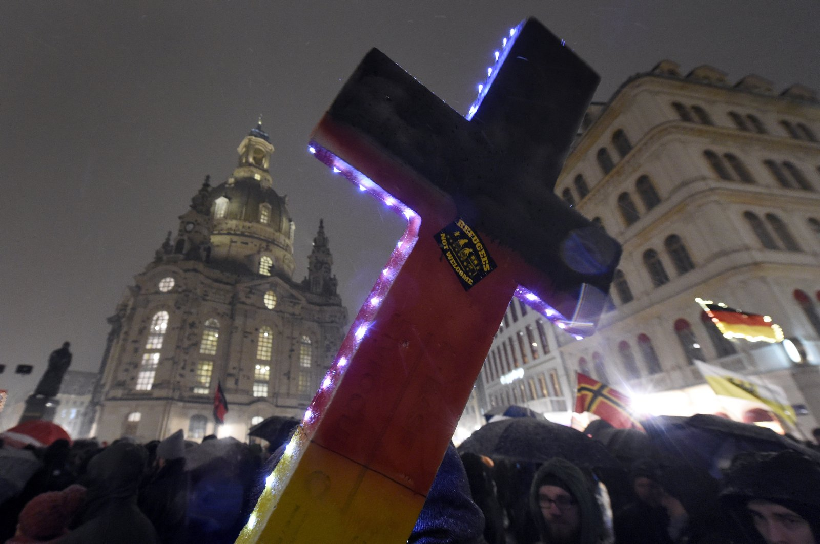 """An illuminated cross with a sticker reading """"refugees not welcome"""" is pictured during a demonstration of PEGIDA close to the Frauenkirche church in Dresden, eastern Germany, Feb. 29, 2016. (AP Photo)"""