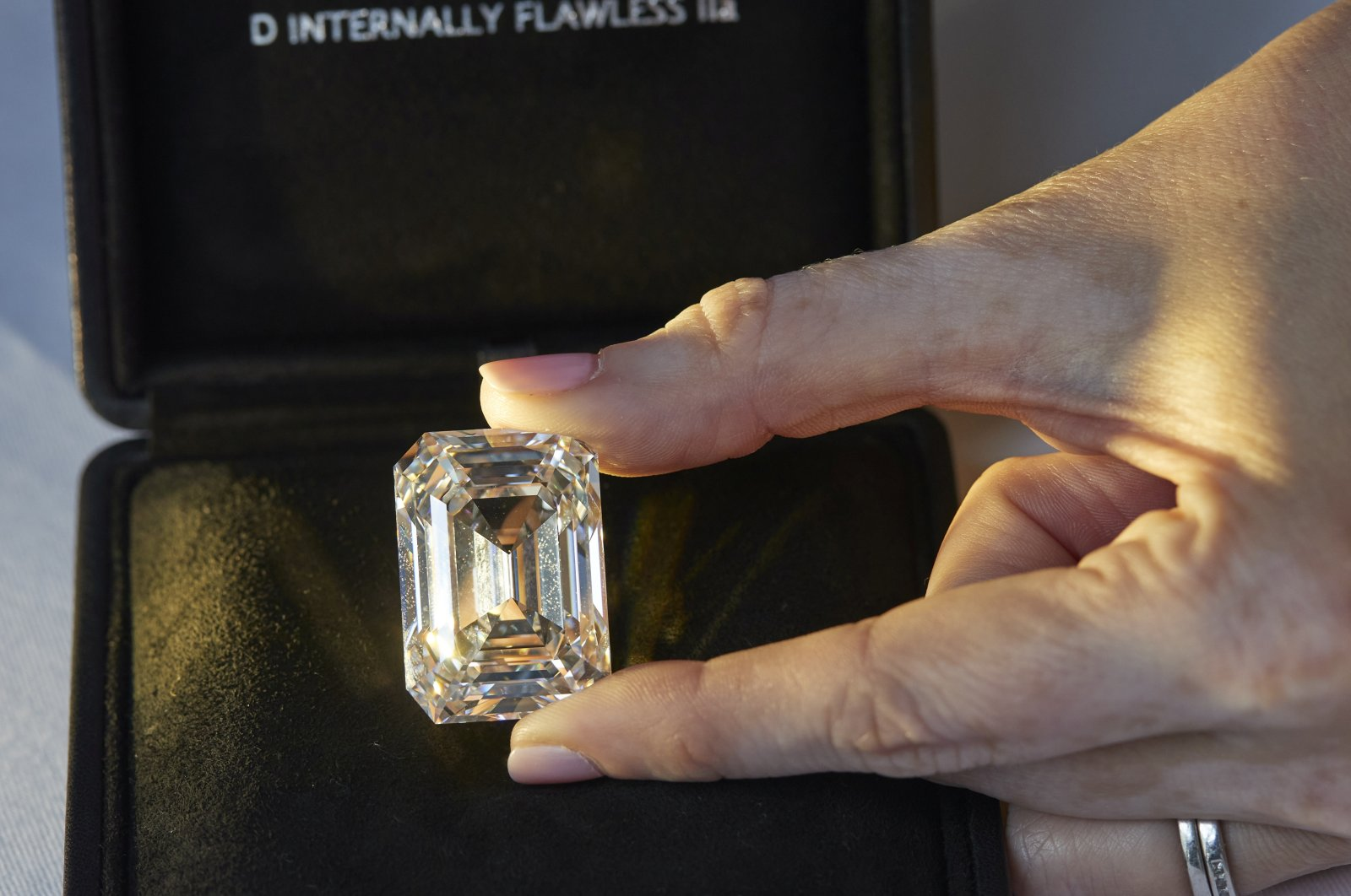 A Christie's staff member holds a D color, internally flawless rectangular step-cut diamond of 100.94 carats during a preview at Christie's before its auction sale in Geneva, Switzerland, May 7, 2021.  (Reuters Photo)