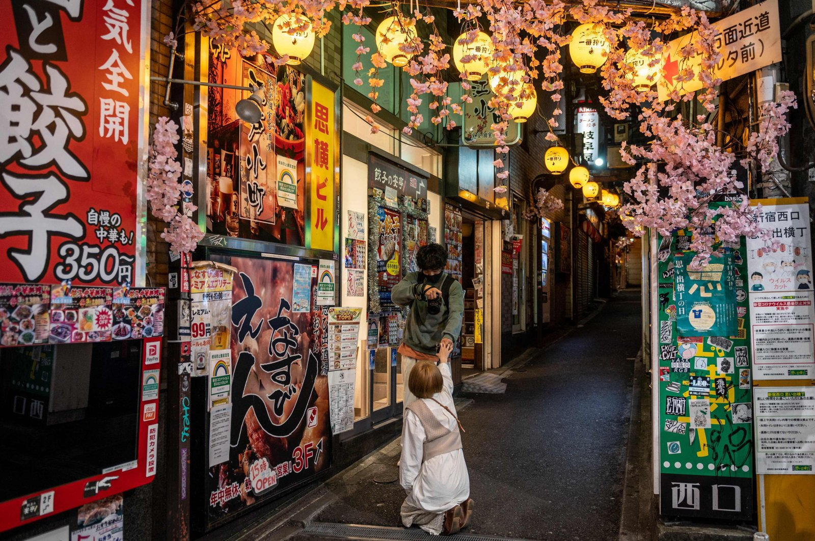 """A couple take pictures at Omoide Yokocho alleyway with closed restaurants in the Shinjuku district during Japan's """"Golden Week"""" holidays, Tokyo, Japan, May 4, 2021. (AFP Photo)"""