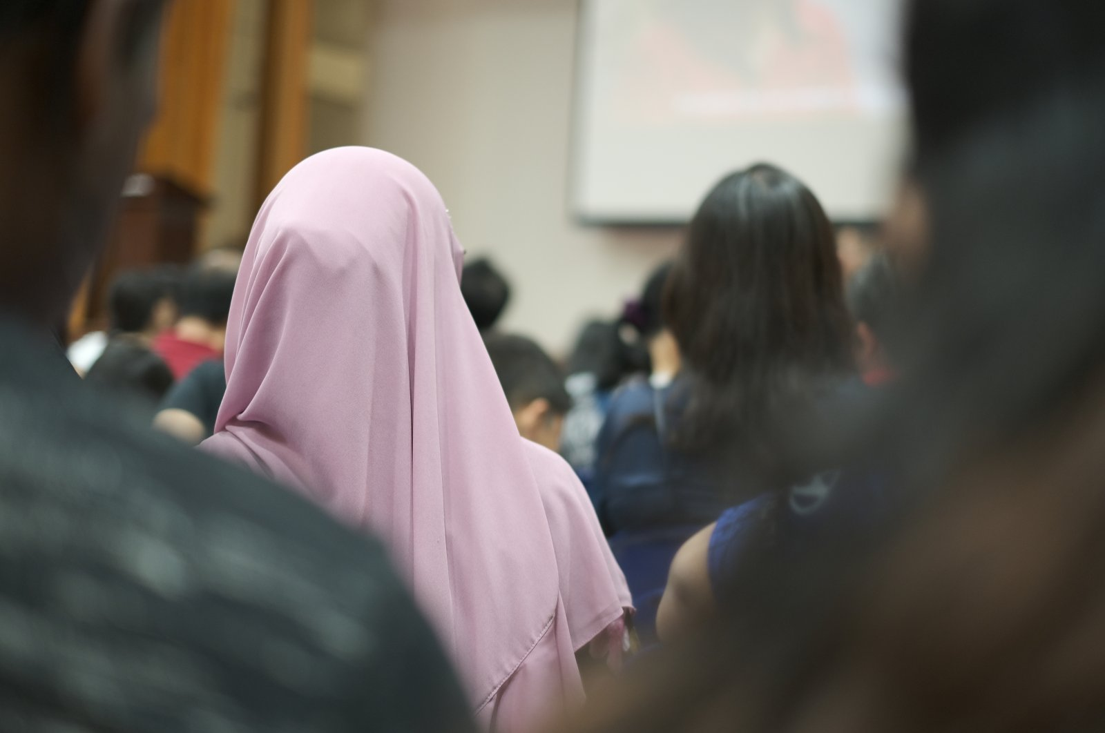 Women wearing a purple headscarf during a gathering of people. (Shutterstock Photo)