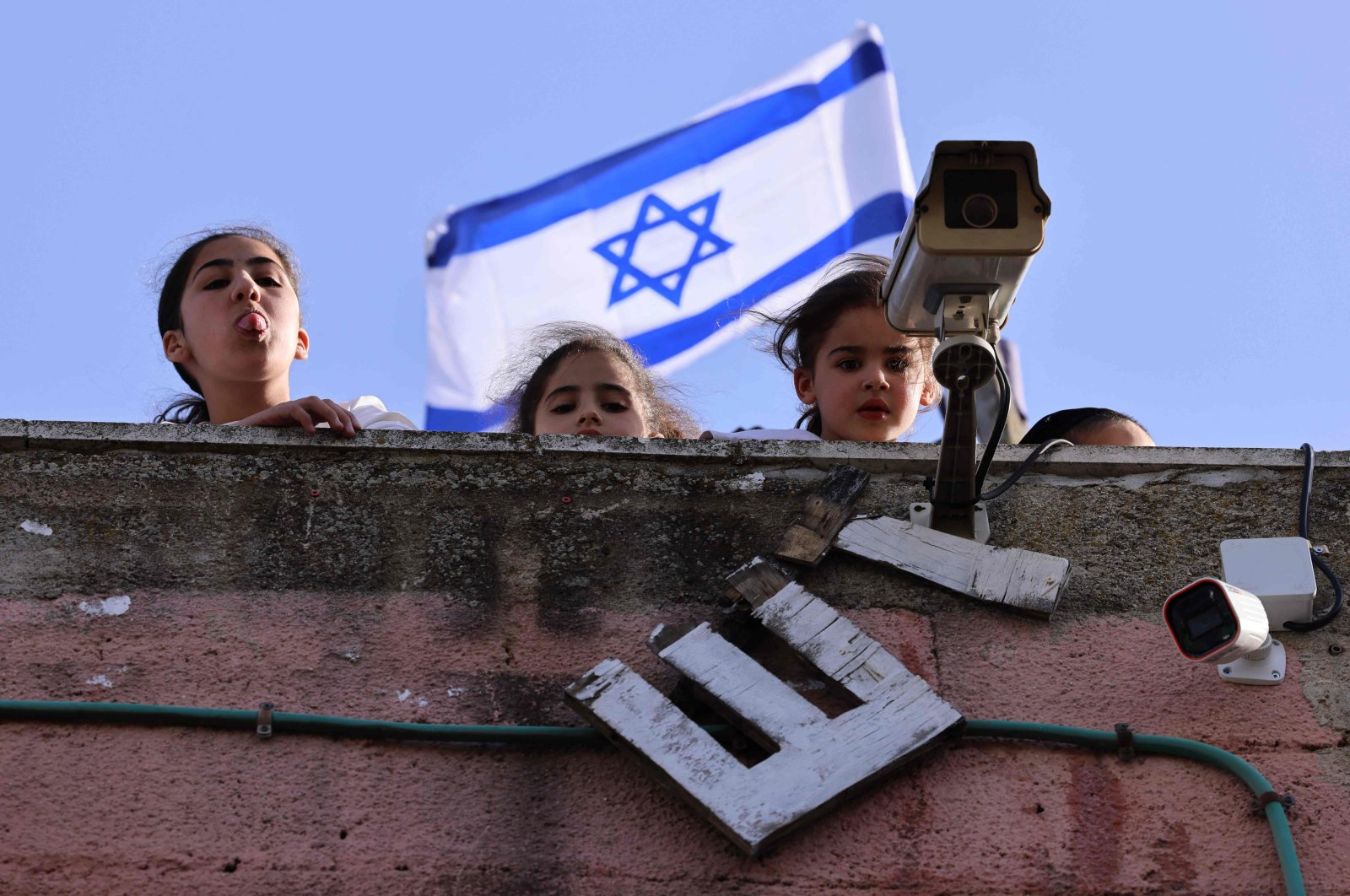 Children of Israeli settlers in the Palestinian neighbourhood of Sheikh Jarrah react as Palestinian and Israeli activists chant slogans in front of their house during a demonstration against the expulsion of Palestinian families from their homes in Israeli-occupied East Jerusalem, April 16, 2021. (AFP Photo)