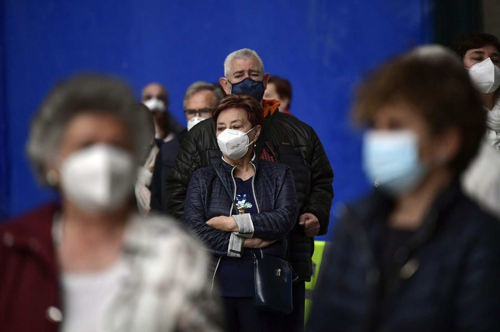 People wearing face masks wait to receive a shot of the Pfizer vaccine during a COVID-19 vaccination campaign, in Pamplona, northern Spain, May 7, 2021. (AP Photo)