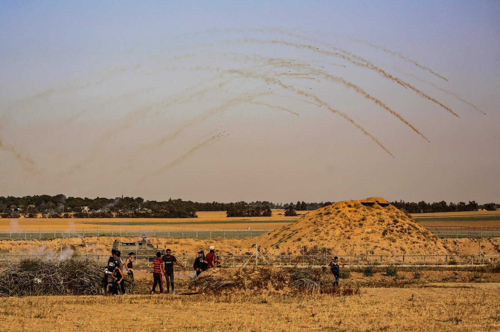 Israeli security forces fire tear gas at Palestinian protesters near the Israel-Gaza border, east of the town of Khan Yunis in the southern Gaza Strip, May 8, 2021. (AFP File Photo)