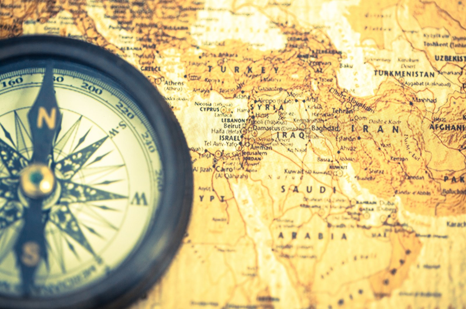 In this illustration photo, an old compass is seen on a vintage world map showing Middle Eastern geography. (Photo by Shutterstock)