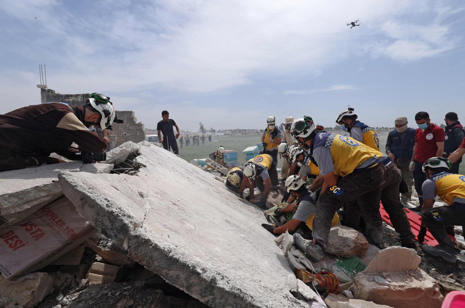 Members of Syria's Civil Defence service (White Helmets) look for wounded people in the rubble after a reported explosion in a depot close to a camp for the internally displaced near al-Fua, in the country's northwestern Idlib province, May 3, 2021. (AFP Photo)