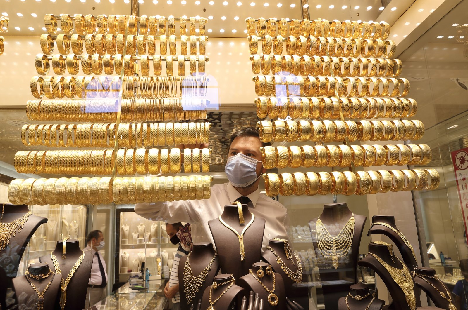 A goldsmith wearing a protective face mask arranges golden bangles at a jewelry shop at the Grand Bazaar in Istanbul, Turkey, Aug. 6, 2020. (Reuters Photo)