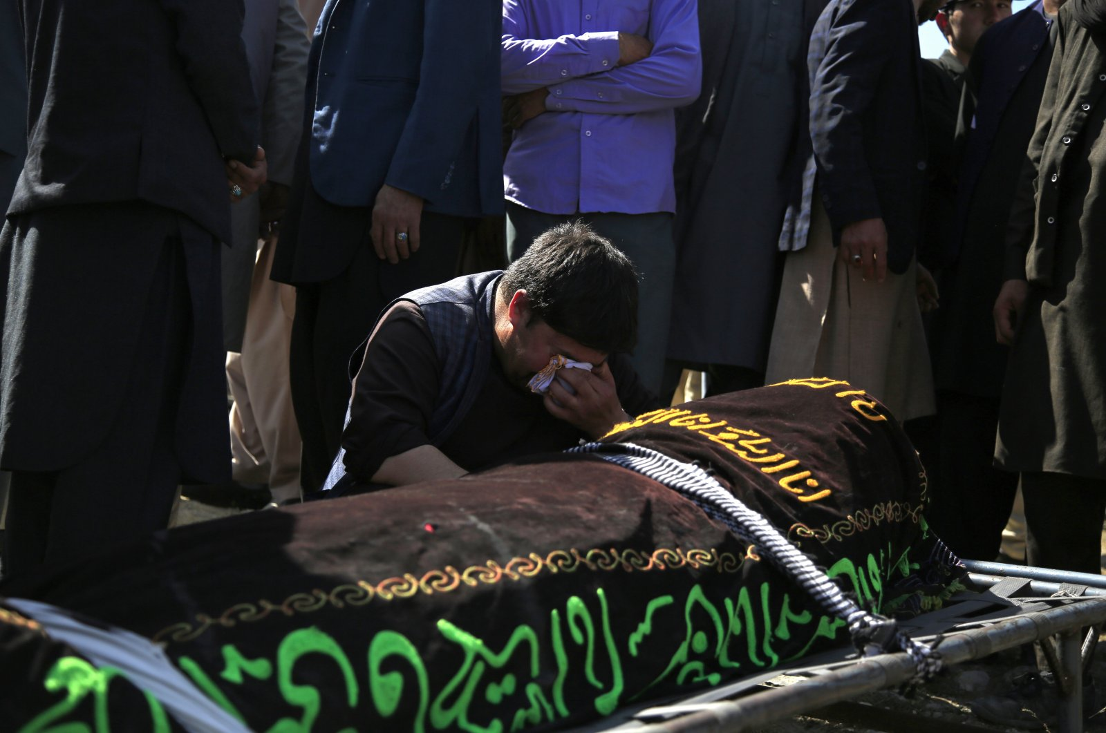 A man cries over the body of a victim of deadly bombings on Saturday near a school, at a cemetery west of Kabul, Afghanistan, May 9, 2021. (AP Photo)