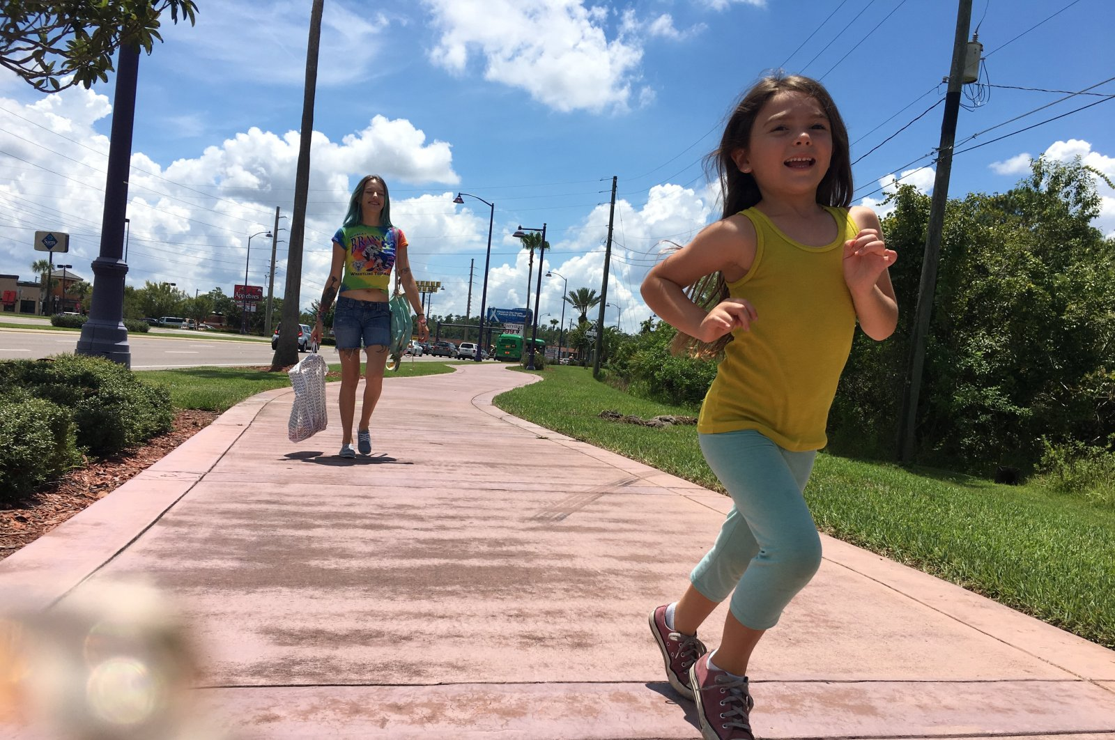 """Brooklynn Prince as """"Moonee"""" runs towards the camera as Bria Vinaite, playing her mother """"Halley"""" in the movie, follows, in a still shot from """"The Florida Project"""" directed by Sean Baker.(Archive Photo)"""