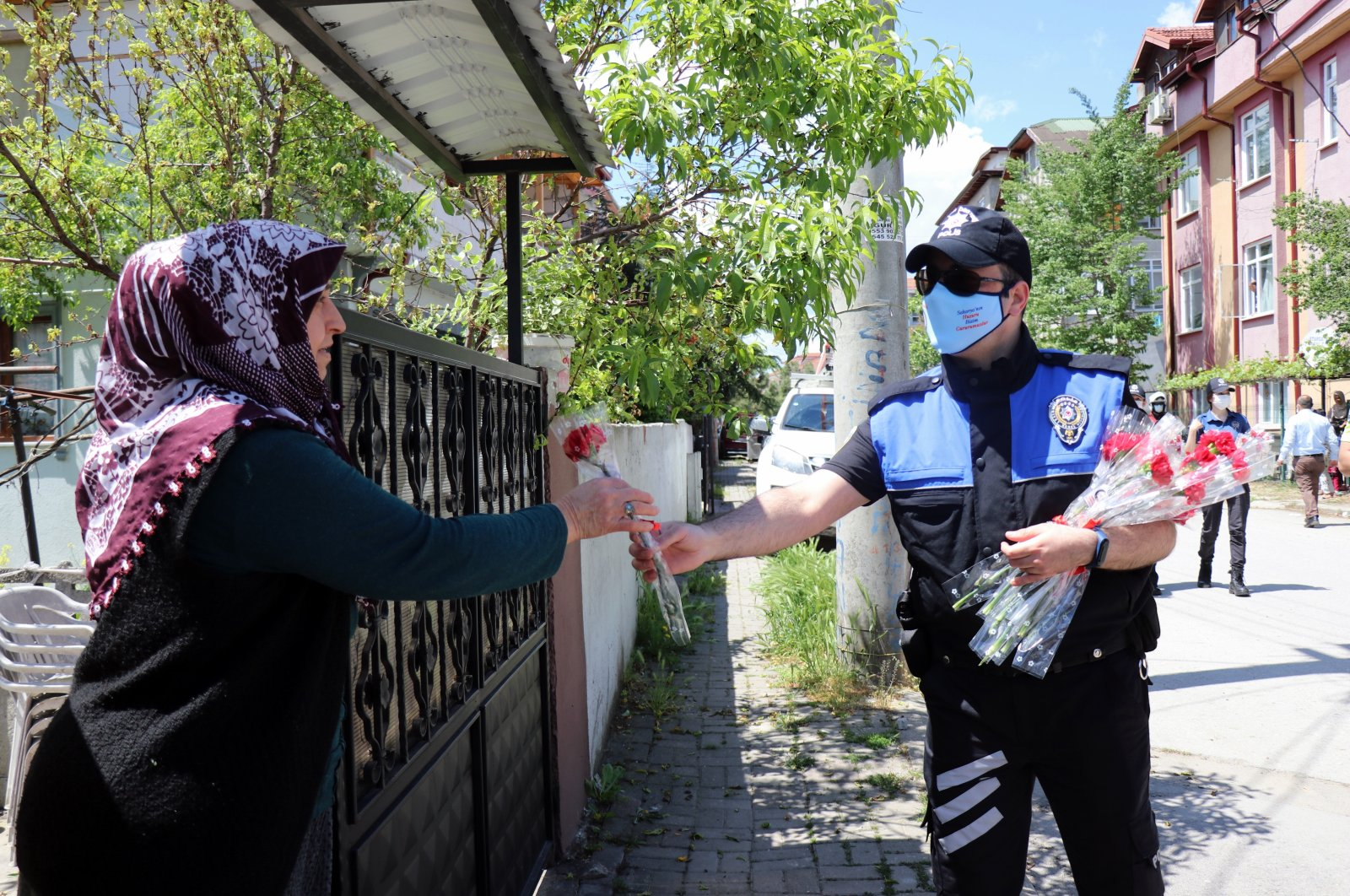 A police officer hands a flower to a woman on the occasion of Mother's Day, in Sakarya, northwestern Turkey, May 9, 2021. (İHA PHOTO)