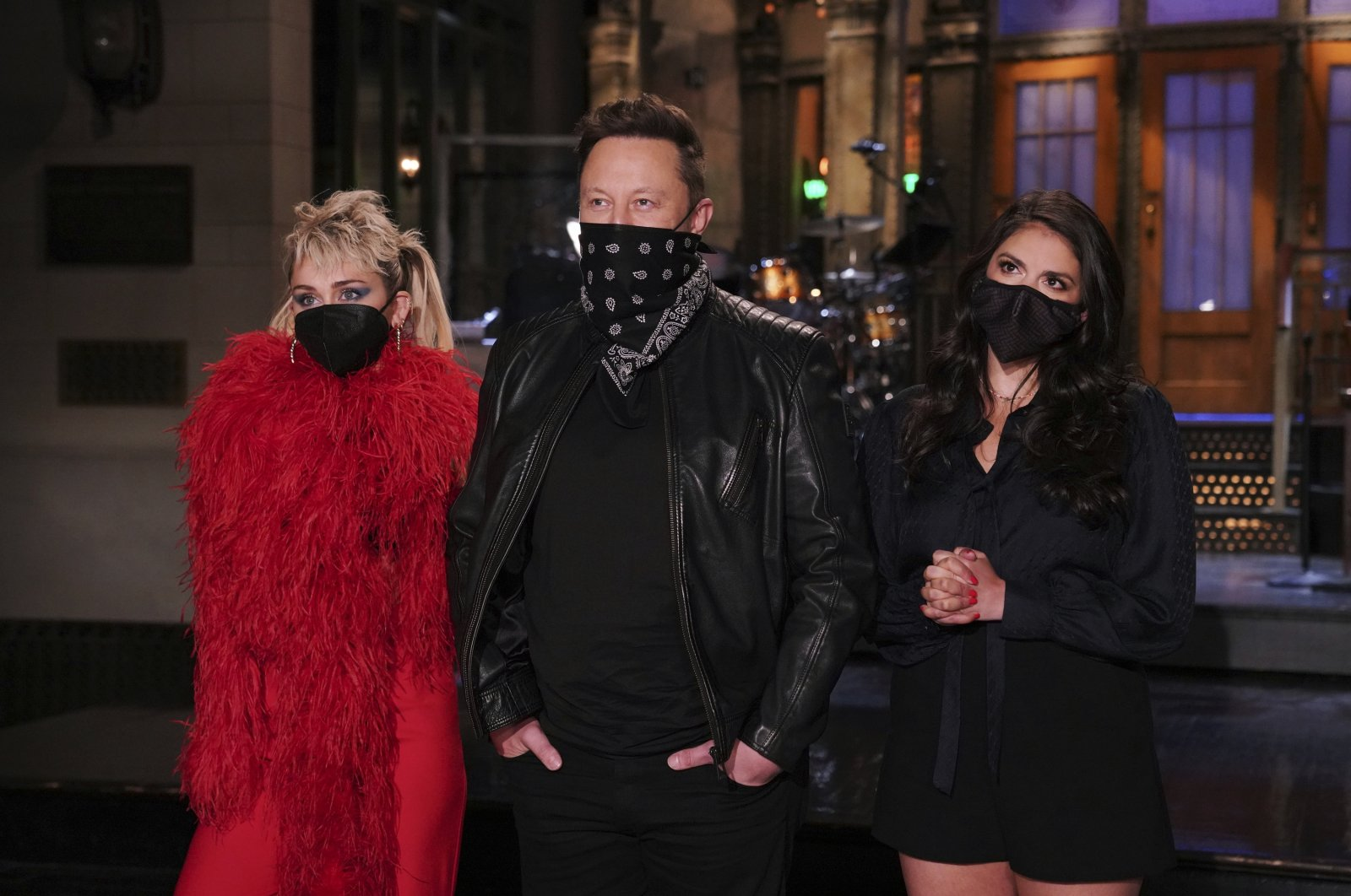 """Musical guest Miley Cyrus (L), host Elon Musk (C), and Cecily Strong (R) appear on stage for the sketch comedy and variety show """"Saturday Night Live,"""" during promos in Studio 8H in New York City, U.S., May 6, 2021. (NBC via AP)"""