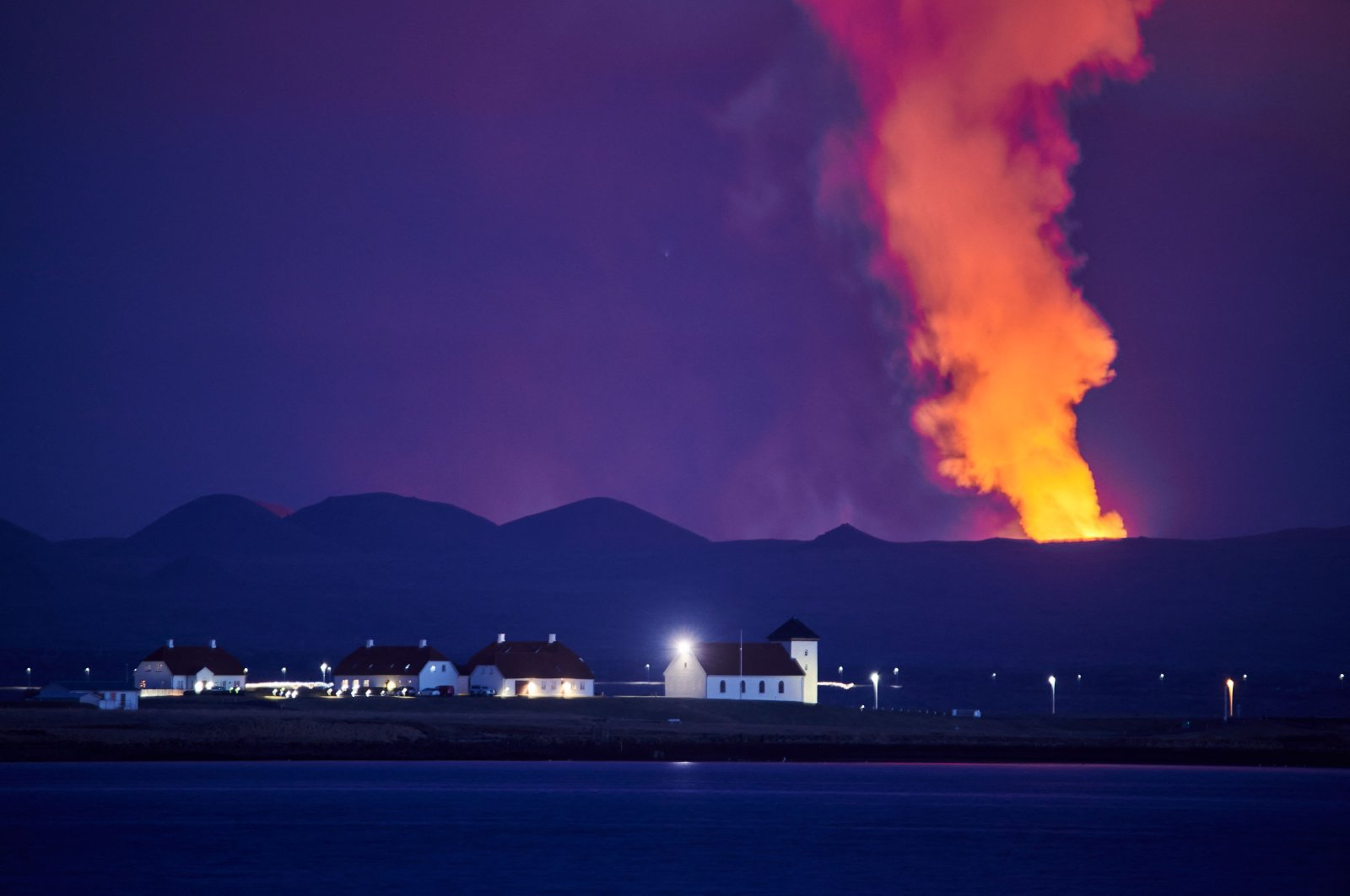 Bessastadir, the official residence of the president of Iceland, is pictured against the backdrop of the smokingFagradalsfjall on the Reykjanes Peninsula, Reykjavik, Iceland, May 5, 2021. (AFP)