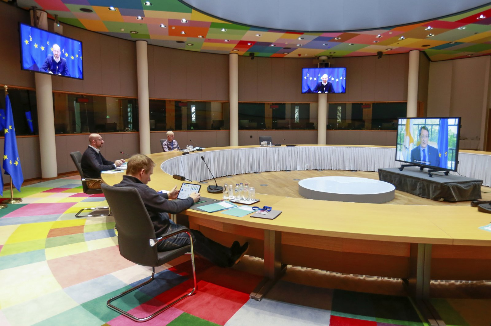 European Council President Charles Michel (L) talks to Cyprus' President Nicos Anastasiades (R) on the screen, during an online meeting at the European Council headquarters in Brussels, Belgium, Friday, April 2, 2021. (Pool Photo via AP)