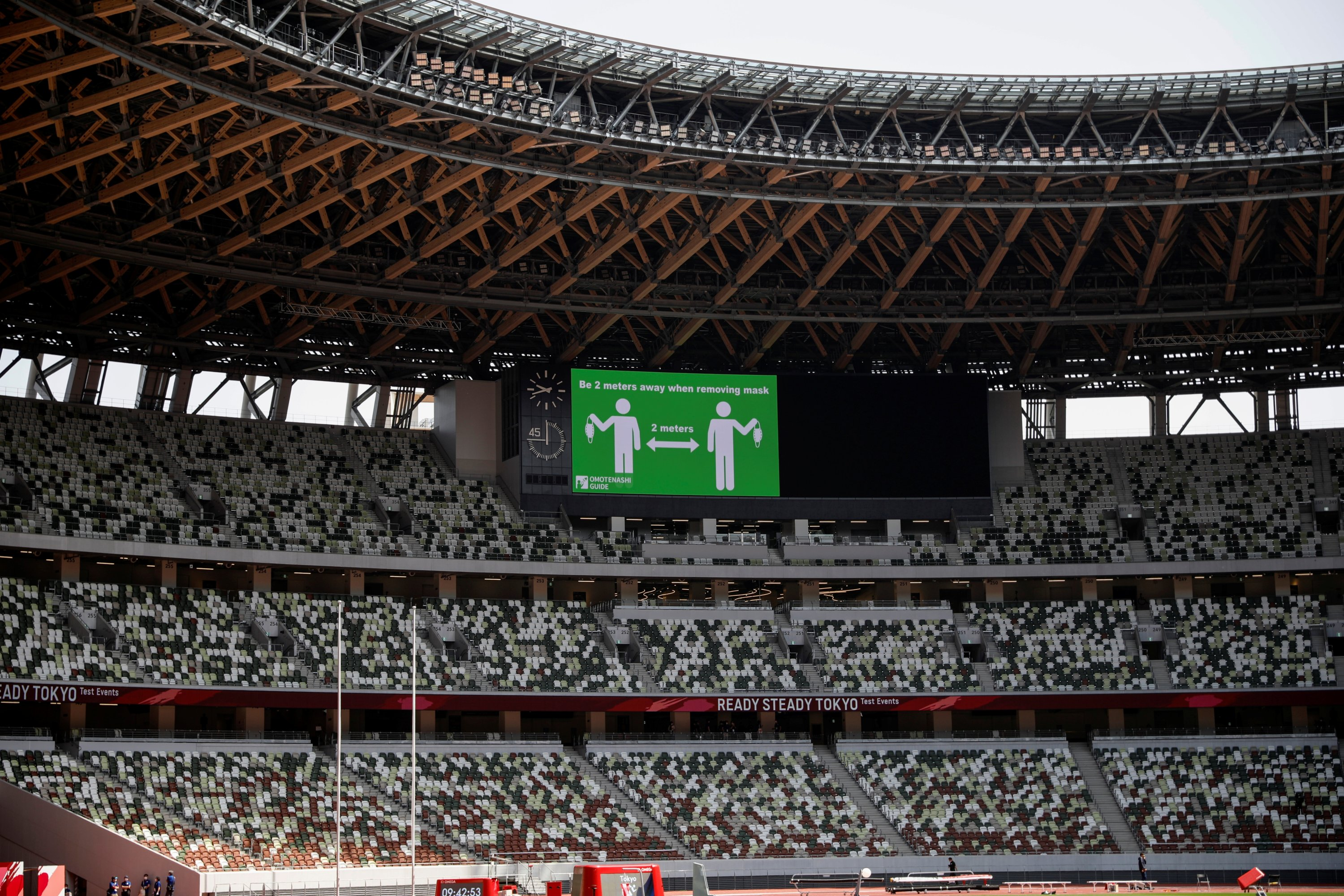 A message regarding safe distancing measures amid the COVID-19 pandemic is shown on a screen at the Olympic Stadium before the start of the morning session of the athletics test event, Tokyo, Japan, May 9, 2021. (Reuters Photo)