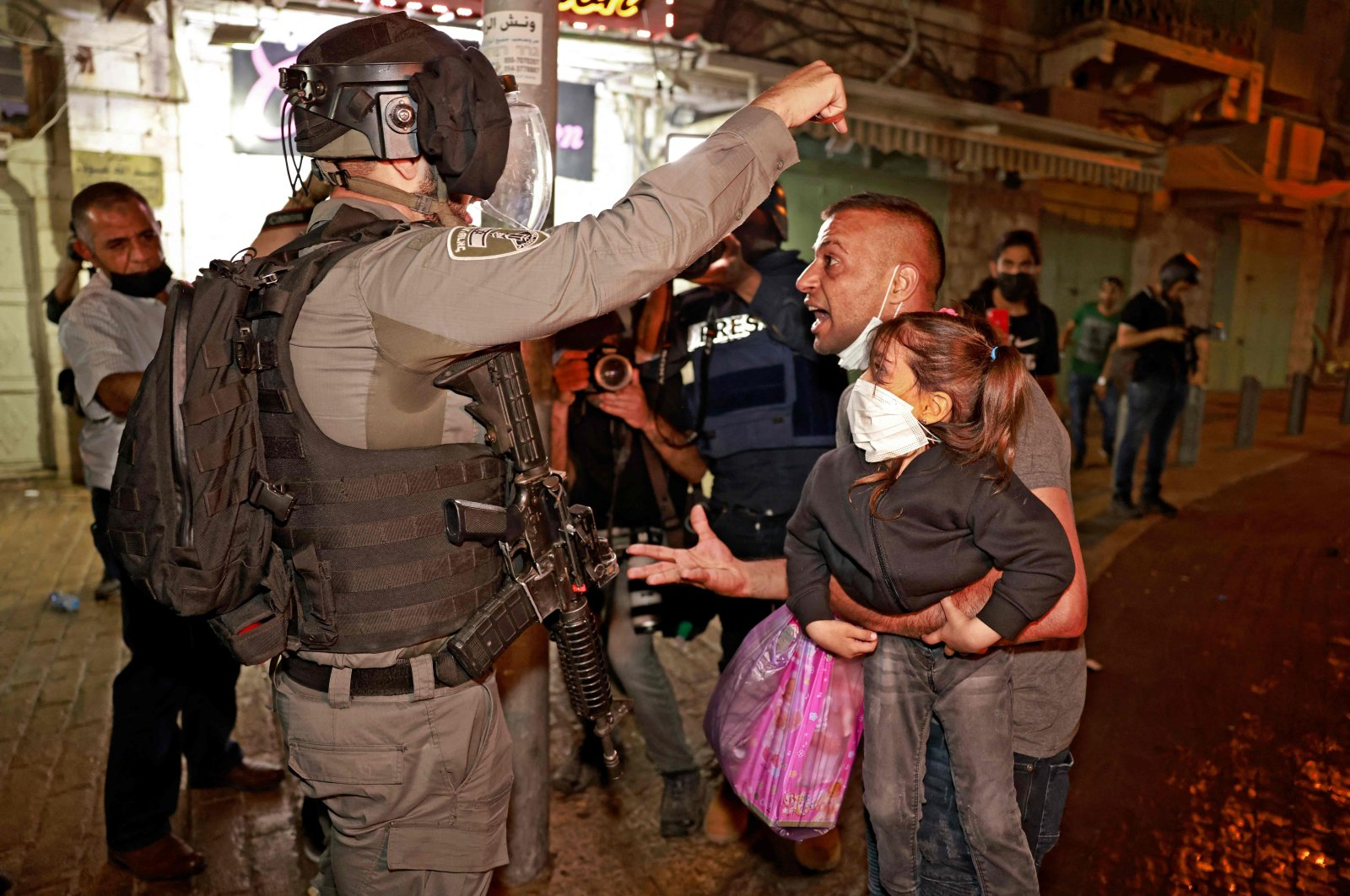 A member of Israeli security forces argues with a Palestinian protester holding a child outside the Damascus Gate in Jerusalem's Old City, East Jerusalem, occupied Palestine, May 9, 2021. (AFP Photo)