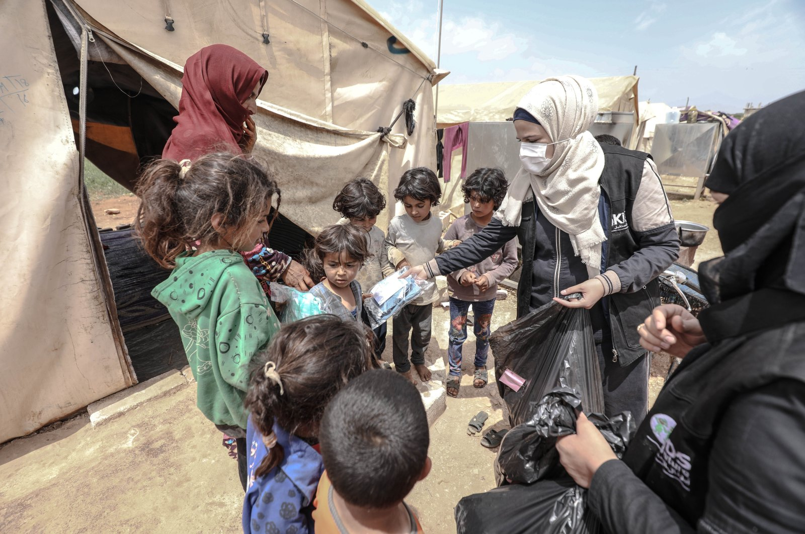 Volunteers distribute clothes to children in a camp in northwestern's Syria's Idlib, May 10, 2021. (AA Photo)