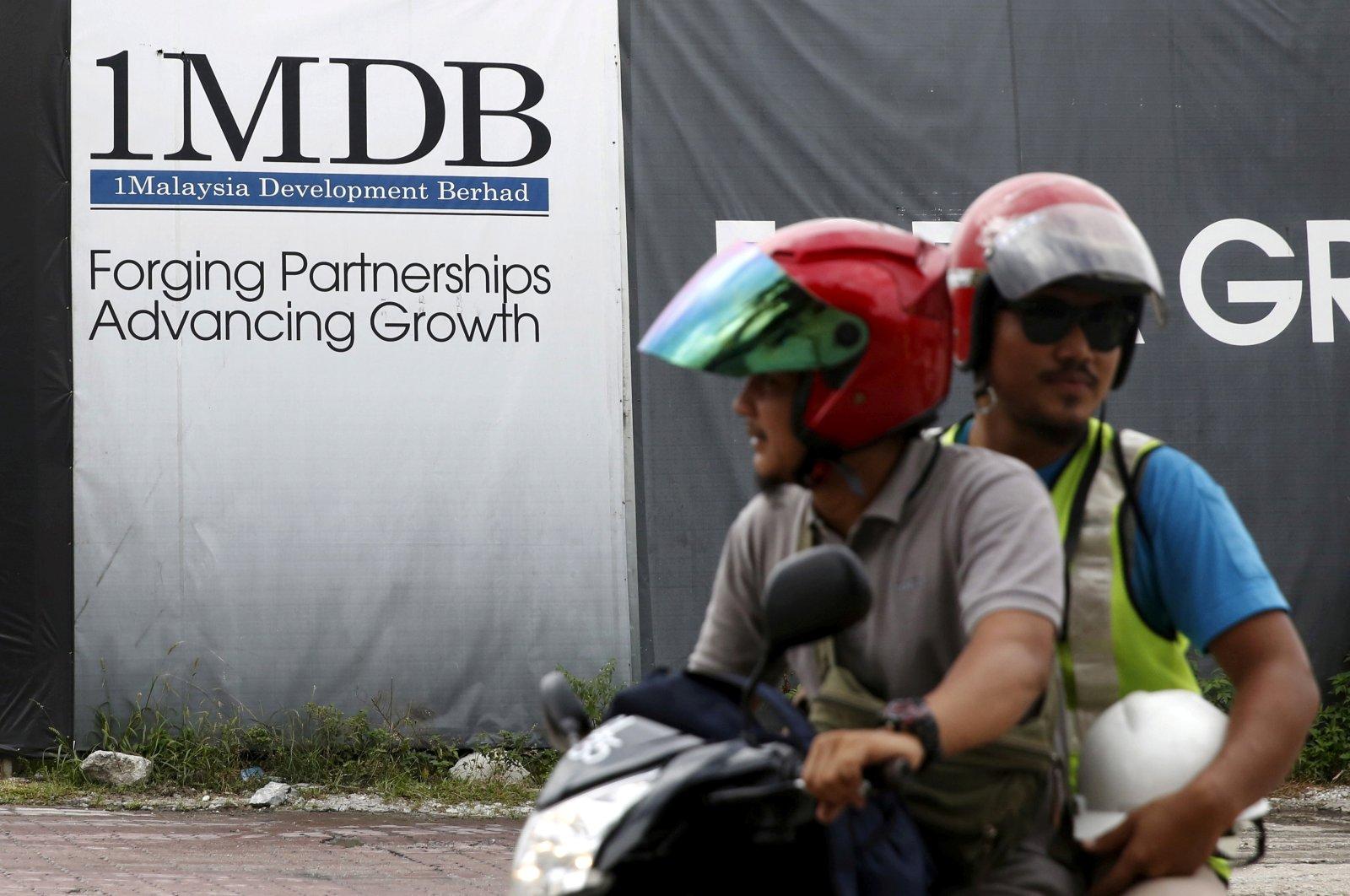 Motorcyclists pass a 1Malaysia Development Berhad (1MDB) billboard at the Tun Razak Exchange development in Kuala Lumpur, Malaysia, Feb. 3, 2016. (Reuters Photo)
