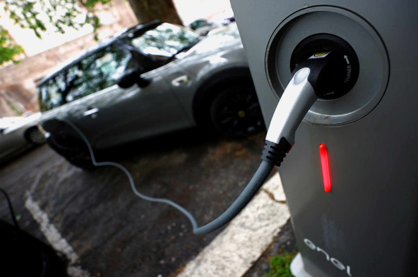 An electric car is seen plugged in at a charging point for electric vehicles in Rome, Italy, April 28, 2021. (Reuters Photo)
