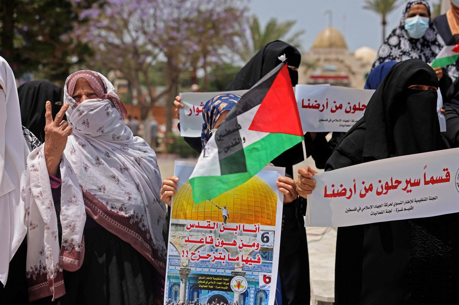 Palestinian women stand with signs and banners during a protest in Gaza City on May 10, 2021 in solidarity with Palestinian families facing Israeli eviction orders in the Sheikh Jarrah neighbourhood of East Jerusalem. (AFP Photo)