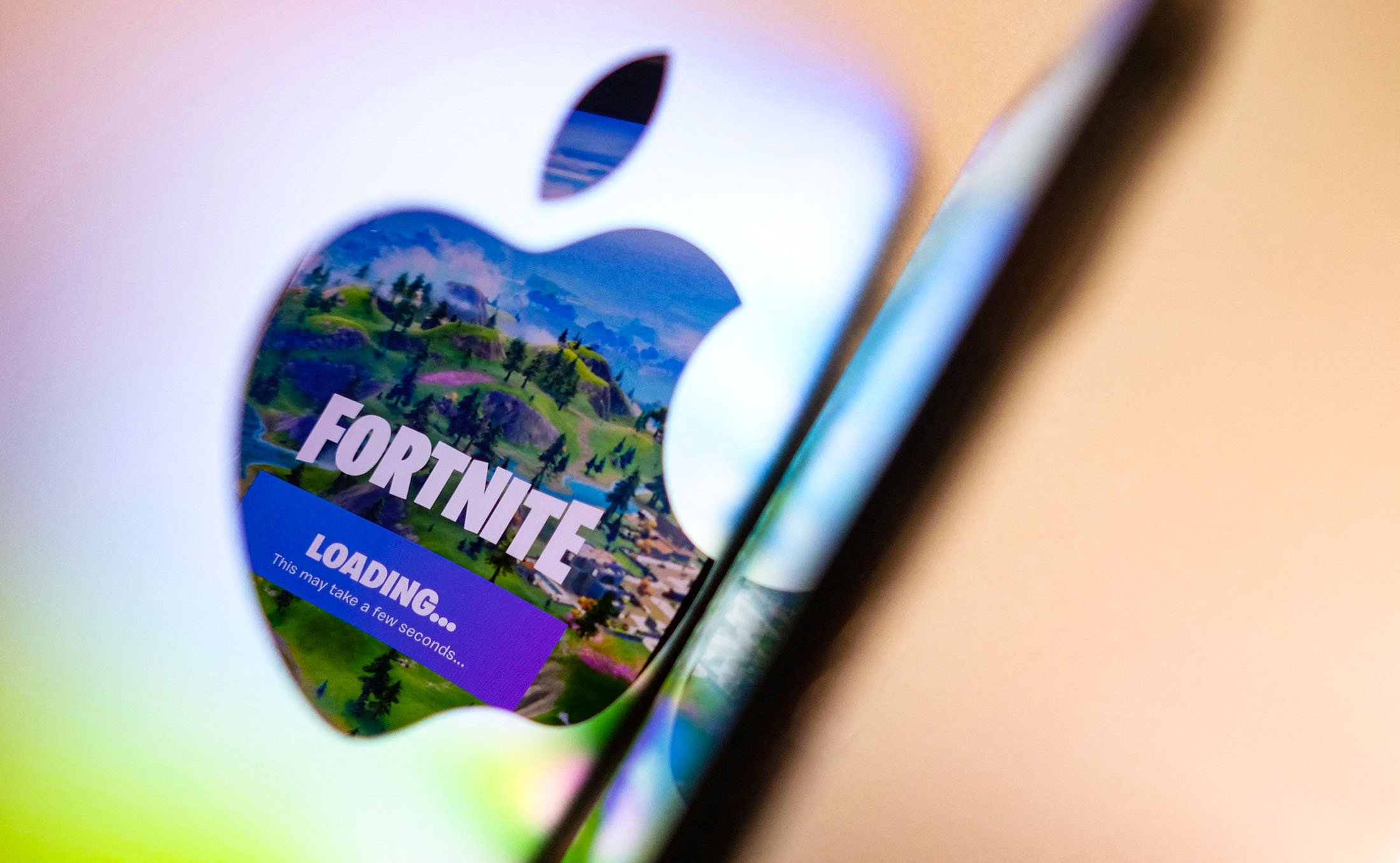 This illustration photo shows the opening screen of Epic Games' Fortnite reflecting onto the Apple logo of the back of an I-mac in Los Angeles, California, U.S., on  May 3, 2021. (AFP Photo)