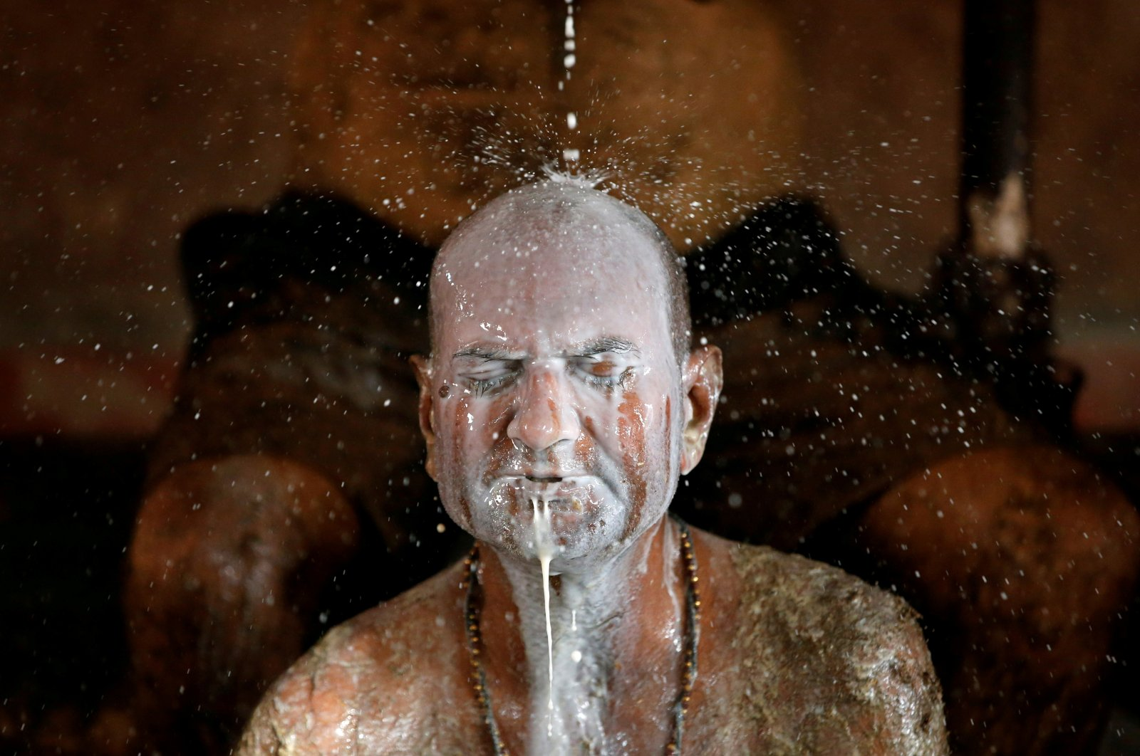 """A man bathes in cow milk to remove cow dung from his body during """"cow dung therapy."""" believing it will boost his immunity to defend against the coronavirus disease at the cow shelter on the outskirts of Ahmedabad, India, May 9, 2021. (Reuters Photo)"""