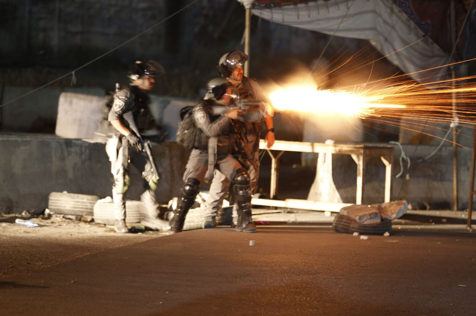 Israeli army soldiers fire tear gas at Palestinians at the Qalandiya checkpoint between Ramallah and Jerusalem, in the occupied West Bank, May 11, 2021. (AFP Photo)